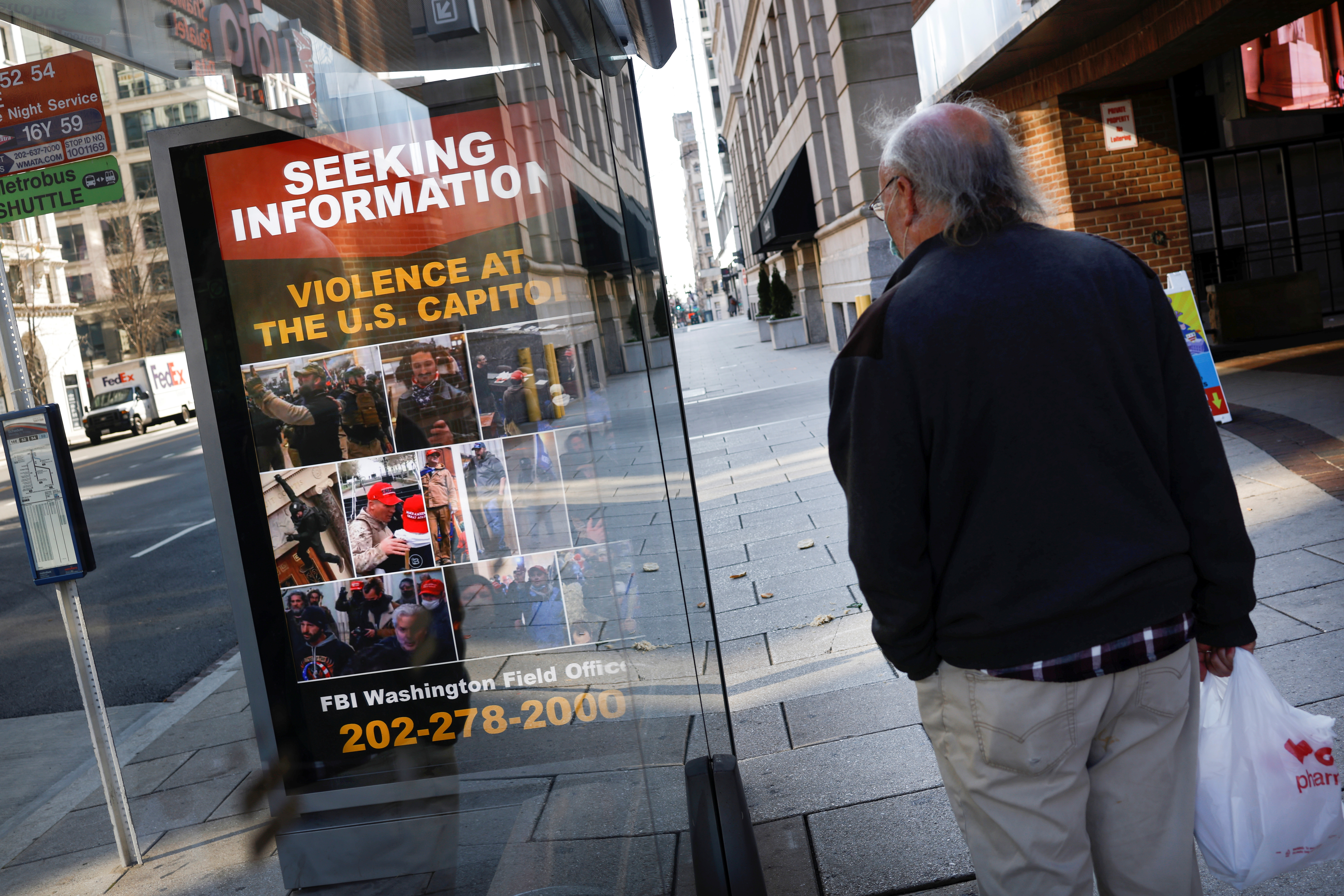 A local resident looks at a billboard with pictures of supporters of U.S. President Donald Trump wanted by the FBI who participated in storming the U.S. Capitol, forcing Congress to postpone a session certifying the results of the 2020 U.S. presidential election, in Washington, U.S., January 13, 2021. REUTERS/Carlos Barria