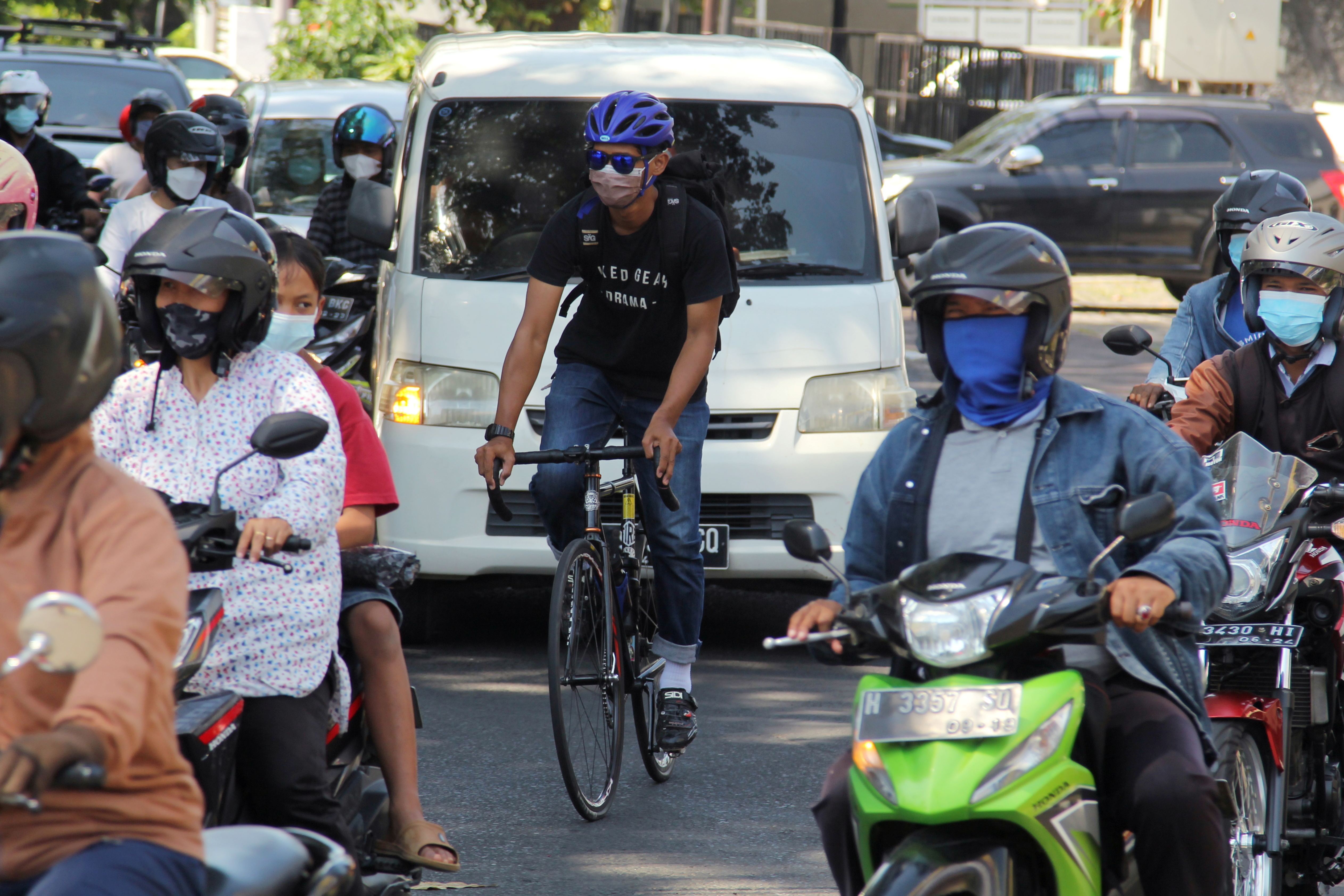 Arrahman Surya Atmaja, a-35-year-old cyclist rides a bicycle through a road on a delivery from a pharmacy to a person self-isolating from the coronavirus disease (COVID-19) in Semarang, Central Java province, Indonesia, July 26, 2021. REUTERS/Budi Purwanto
