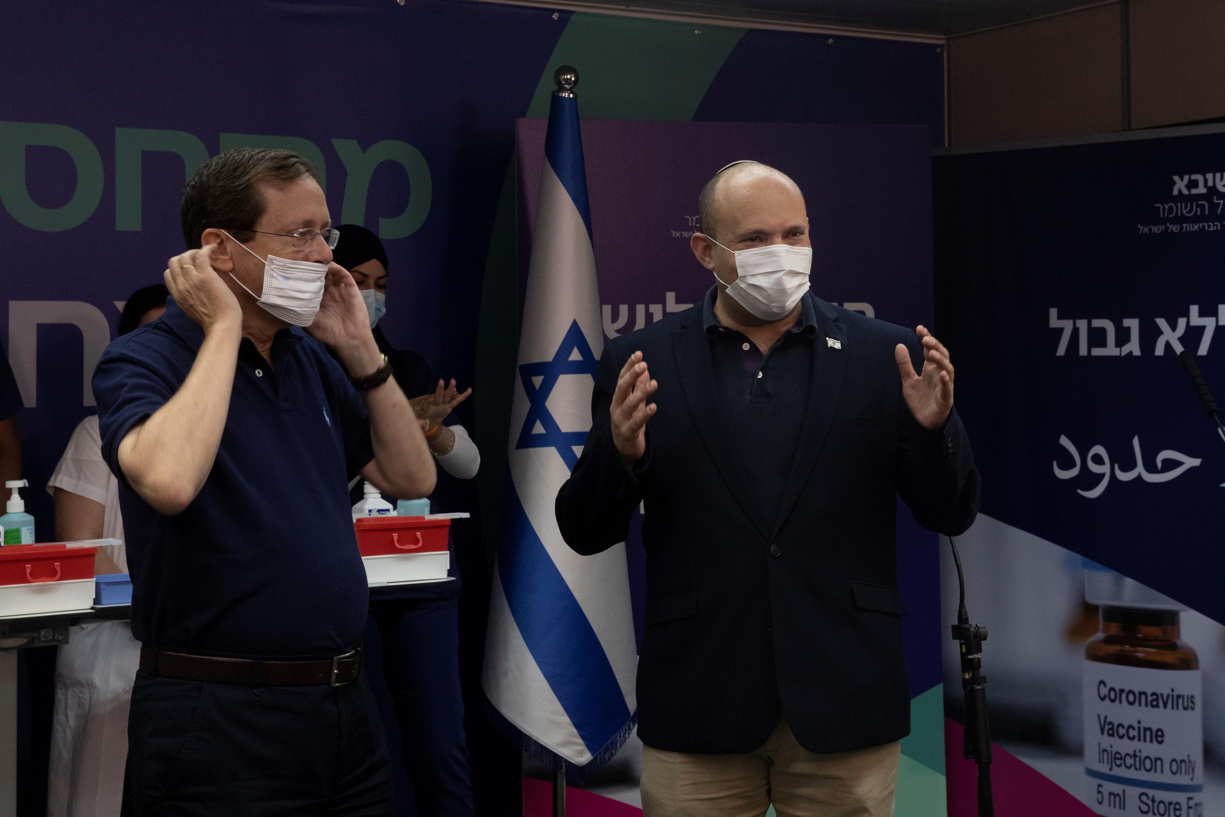 Israeli President Isaac Herzog adjusts his mask as Prime Minister Naftali Bennett, speaks to members of the media after Herzog received a third dose of coronavirus disease (COVID-19) vaccine at Sheba Medical Center in Ramat Gan, Israel, July 30, 2021. Maya Alleruzzo/Pool via REUTERS