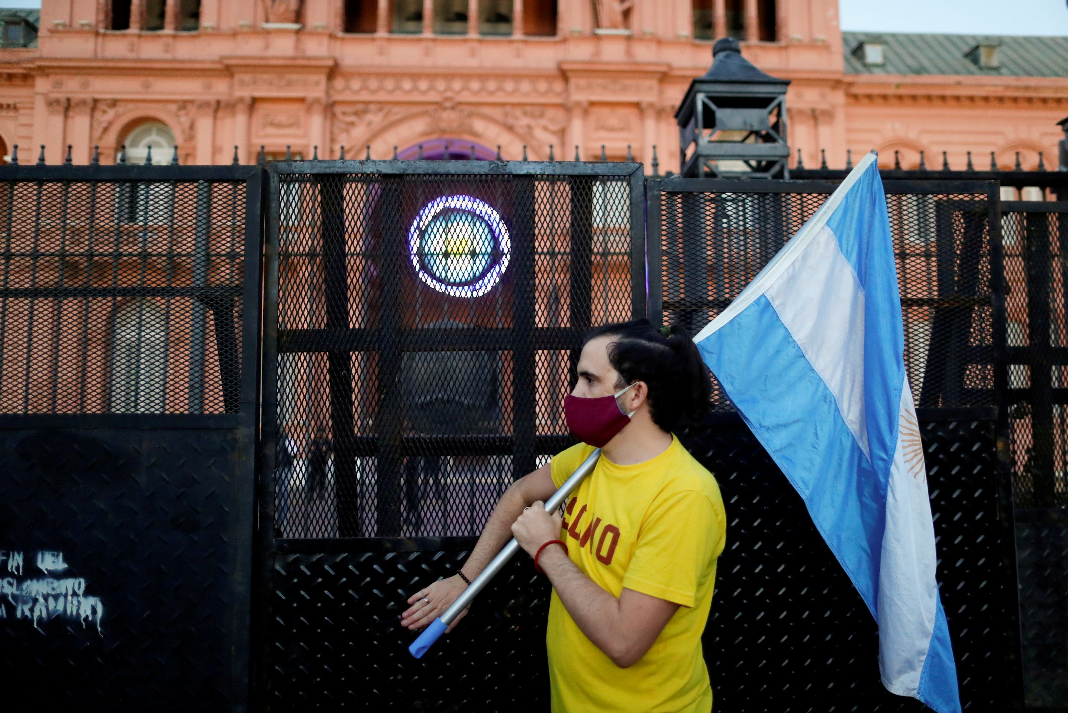 A demonstrator holds an Argentinian flag as they protest against Argentina's President Alberto Fernandez's lockdown measures to curb the spread of the coronavirus (COVID-19) disease, outside Casa Rosada presidential palace in Buenos Aires, Argentina, April 17, 2021. REUTERS/Agustin Marcarian/