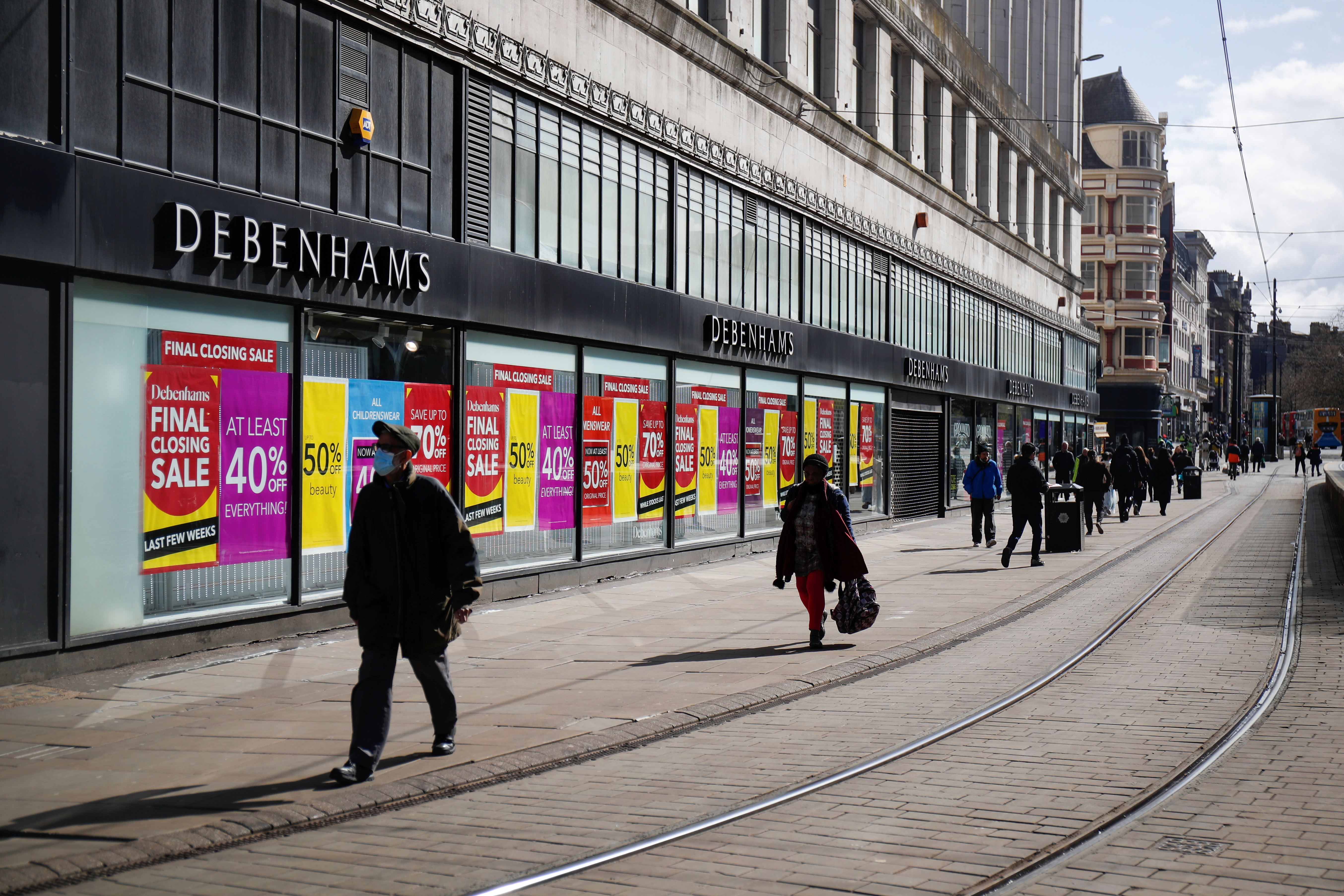 People walk past shops, as the coronavirus disease (COVID-19) restrictions begin to ease, in Manchester, Britain, April 9, 2021. REUTERS/Molly Darlington