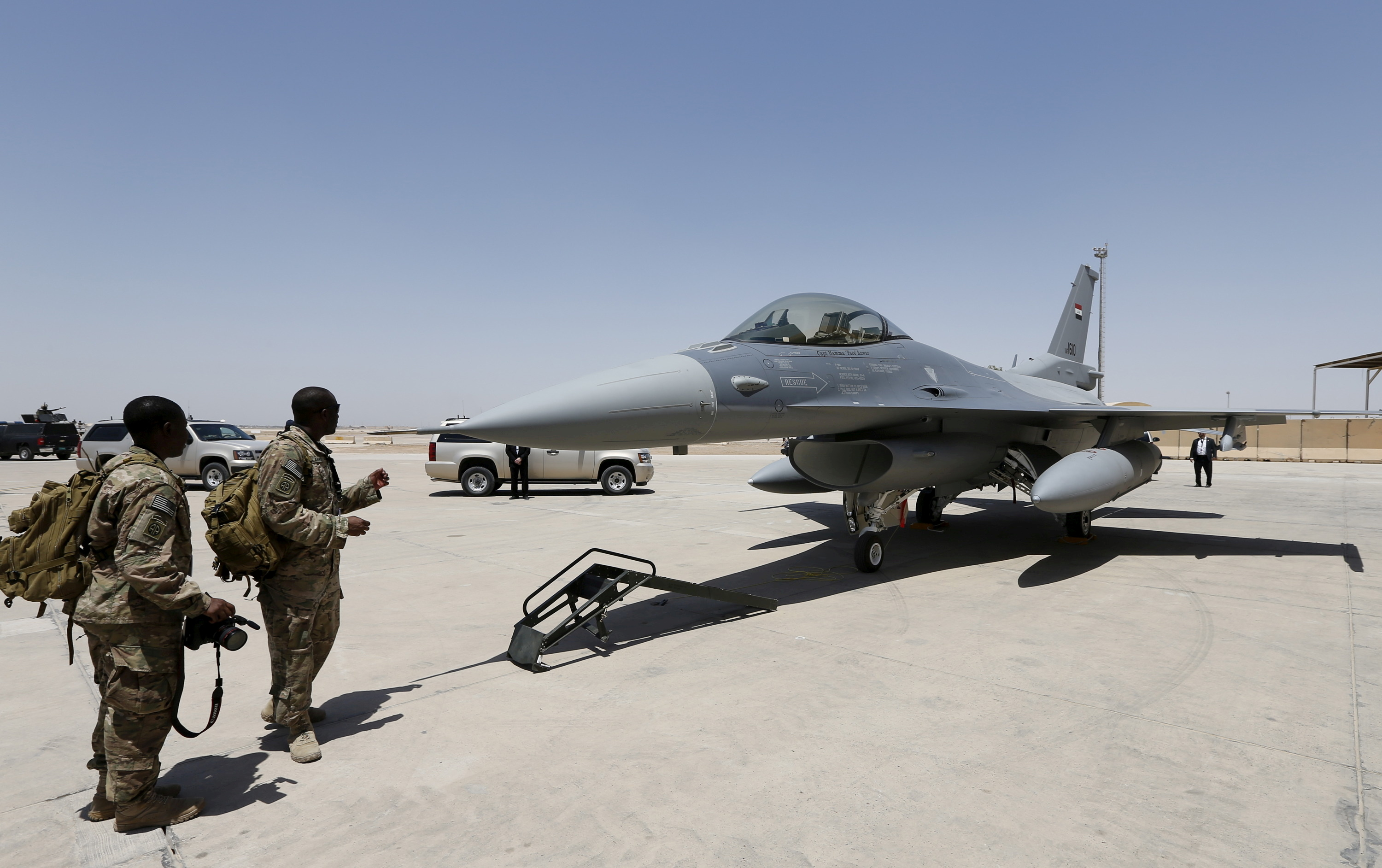 U.S. Army soldiers look at an F-16 fighter jet during an official ceremony to receive four such aircraft from the United States, at a military base in Balad, Iraq, July 20, 2015. REUTERS/Thaier Al-Sudani/File Photo