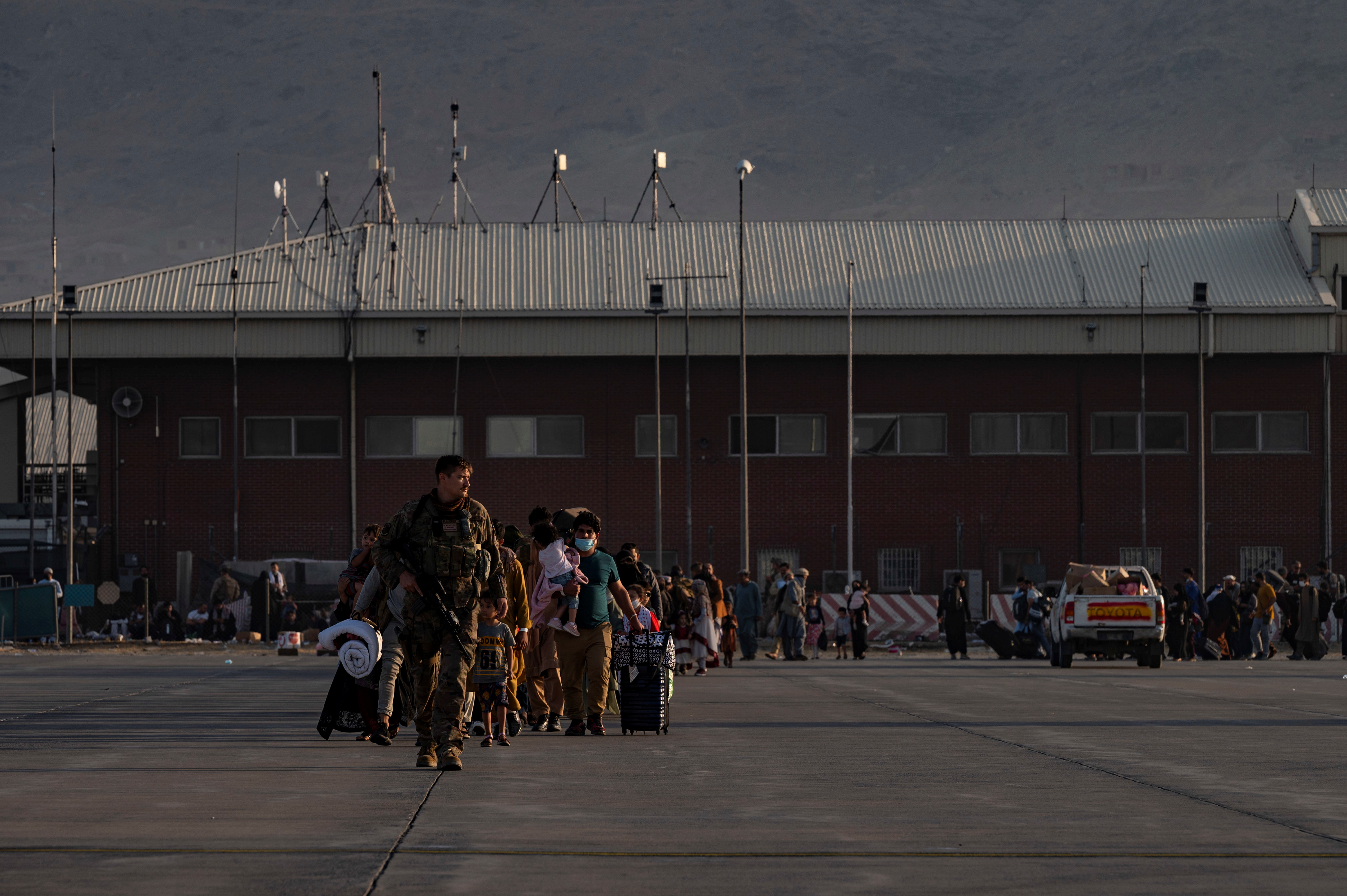 A U.S. Air Force Airman guides qualified evacuees aboard a U.S. Air Force C-17 Globemaster III at Hamid Karzai International Airport (HKIA), Afghanistan, August 24, 2021.  U.S. Air Force/Senior Airman Taylor Crul/Handout via REUTERS THIS IMAGE HAS BEEN SUPPLIED BY A THIRD PARTY.