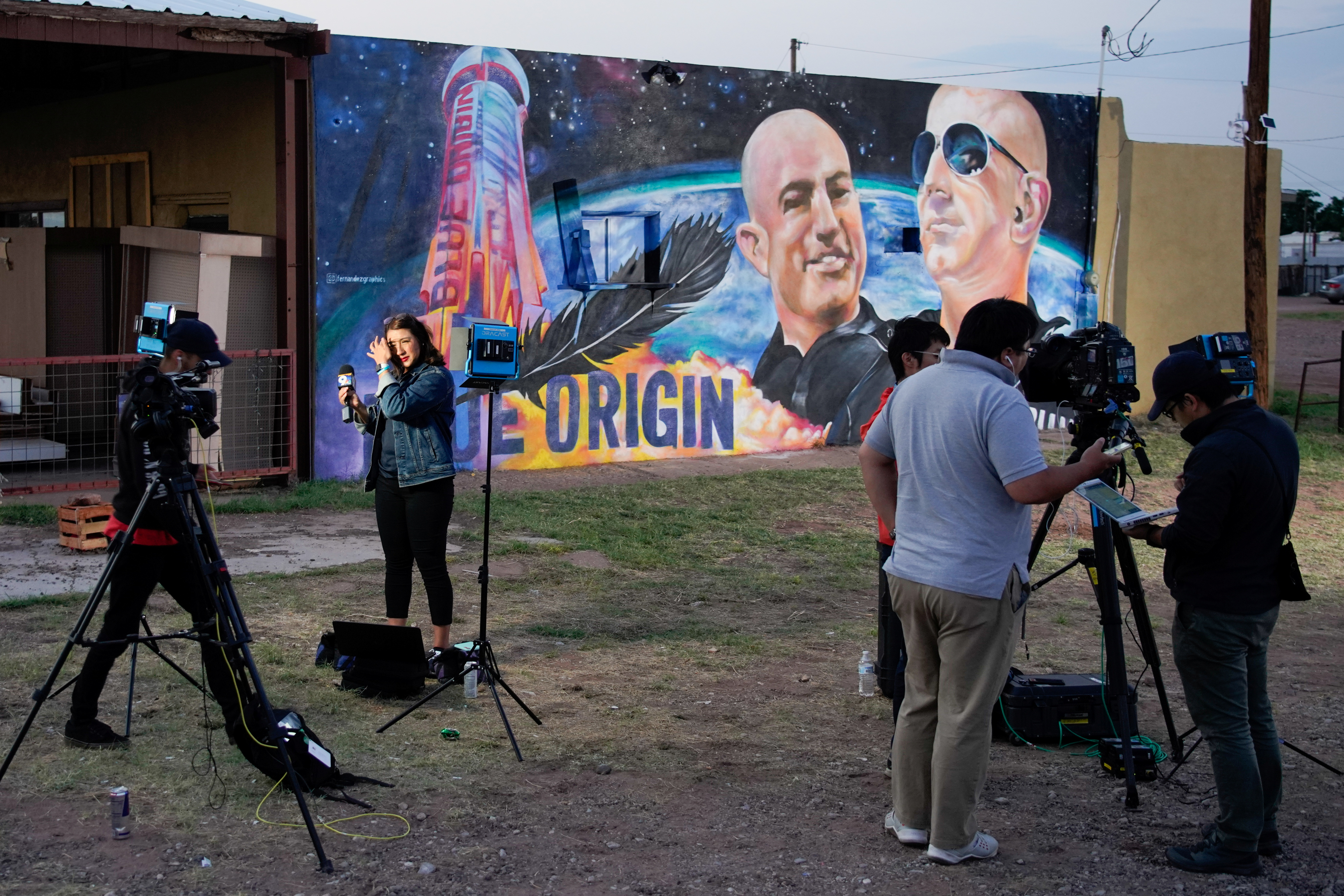 News Channel 9 Reporter Celina Quintana Ortiz prepares to go live in front of a Blue Origin Mural depicting Jeff and Mark Bezos, in Van Horn, Texas, U.S., July 20, 2021. REUTERS/Paul Ratje