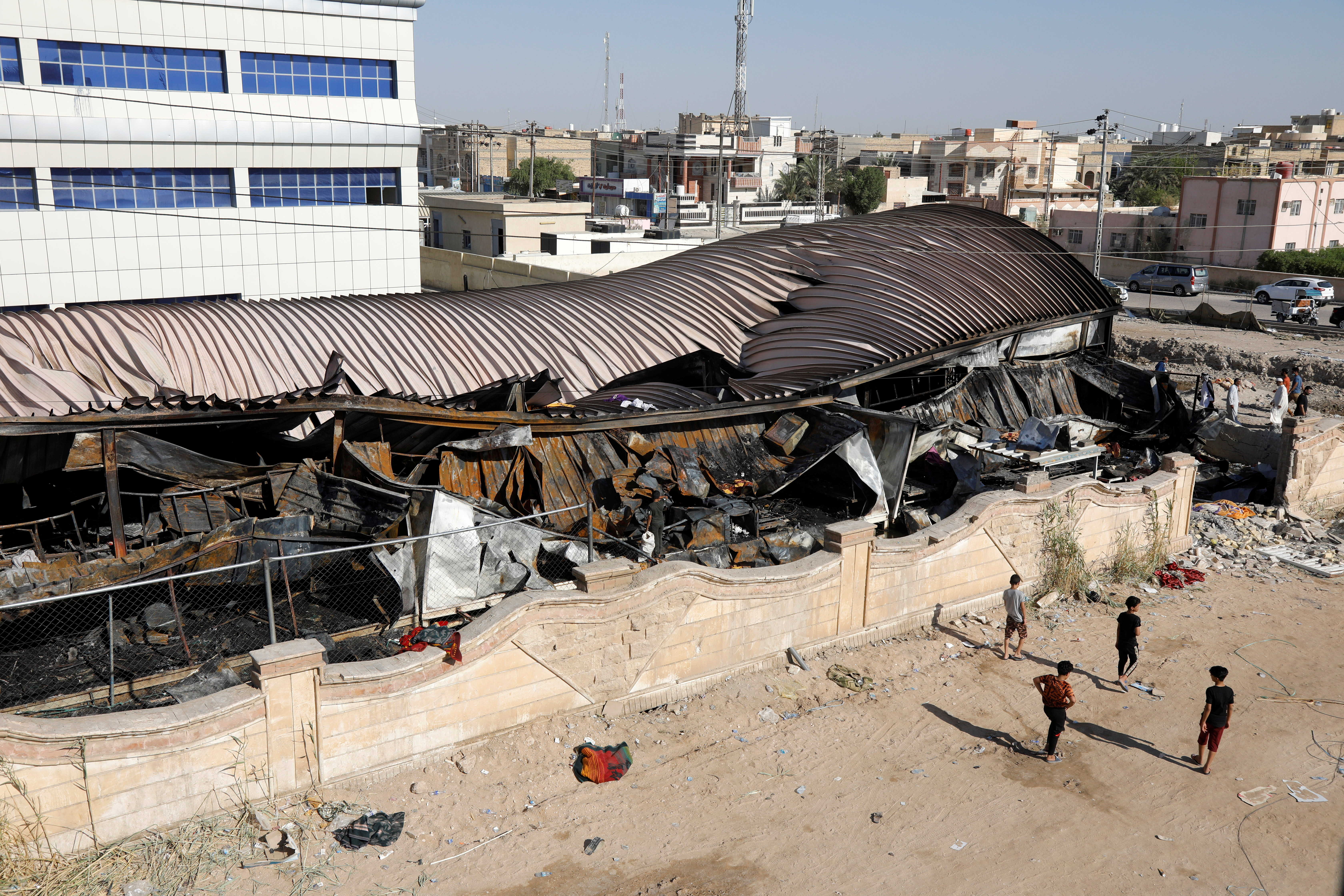 People walk past the damaged al-Hussain coronavirus hospital after a fire broke out in Nassiriya, Iraq, July 13, 2021. REUTERS/Khalid al-Mousily