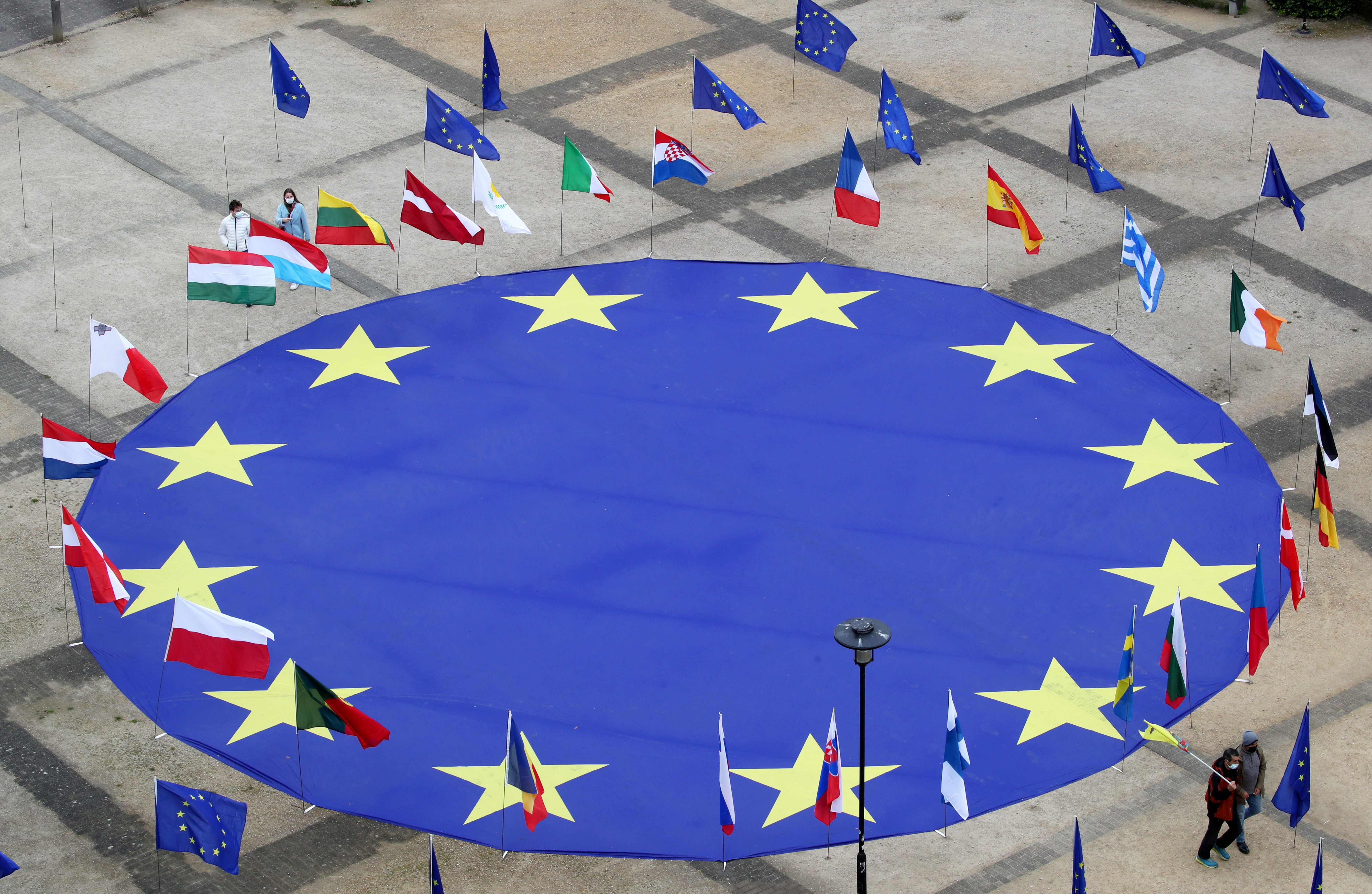 A large European Union flag lies at the centre of Schuman square, outside the European Commission headquarters, on the eve of Europe Day, commemorating the declaration made by Robert Schuman in 1950, in Brussels, Belgium, May 8, 2021.  REUTERS/Yves Herman