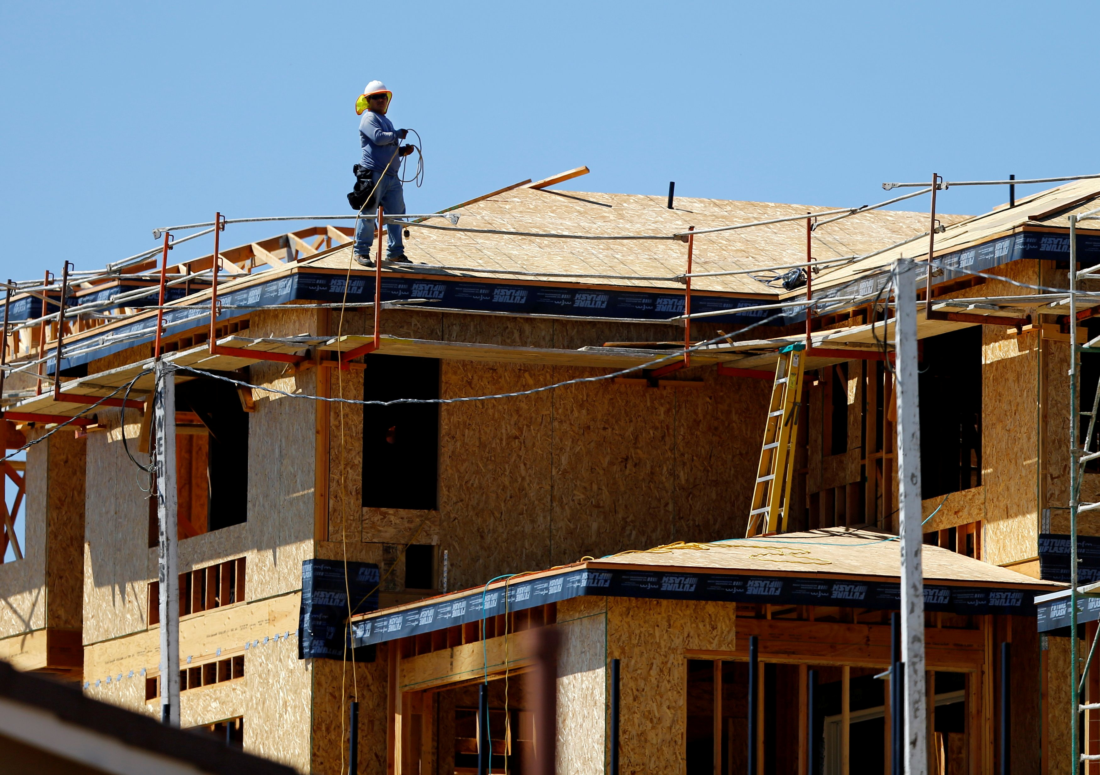 A worker walks on the roof of a new home under construction in Carlsbad, California September 22, 2014. REUTERS/Mike Blake/File Photo