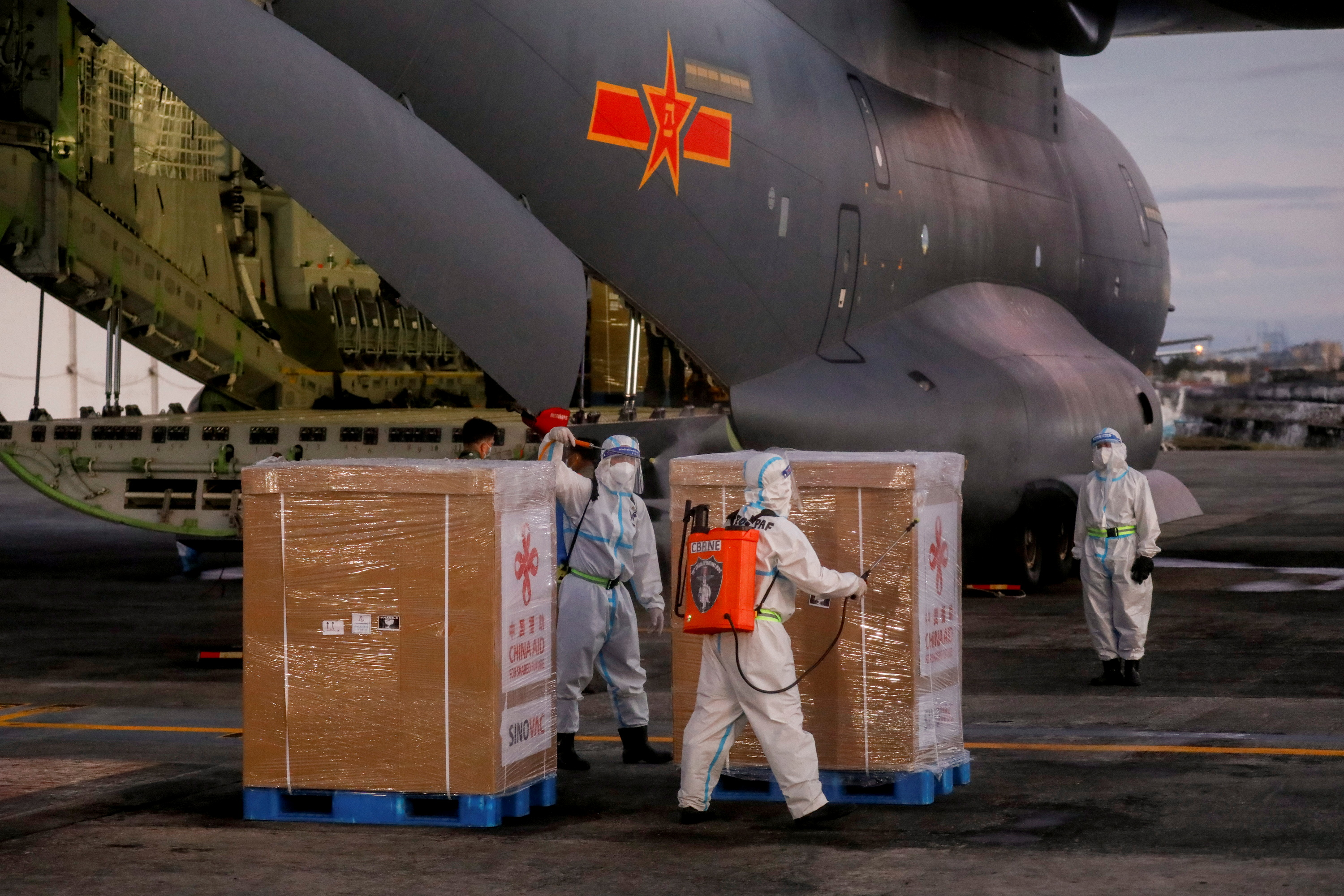 Workers in hazmat suits disinfect boxes of Sinovac Biotech's CoronaVac vaccine against coronavirus disease (COVID-19) after unloading them from a Chinese military aircraft at Villamor Air Base in Pasay, Metro Manila, Philippines, February 28, 2021. REUTERS/Eloisa Lopez