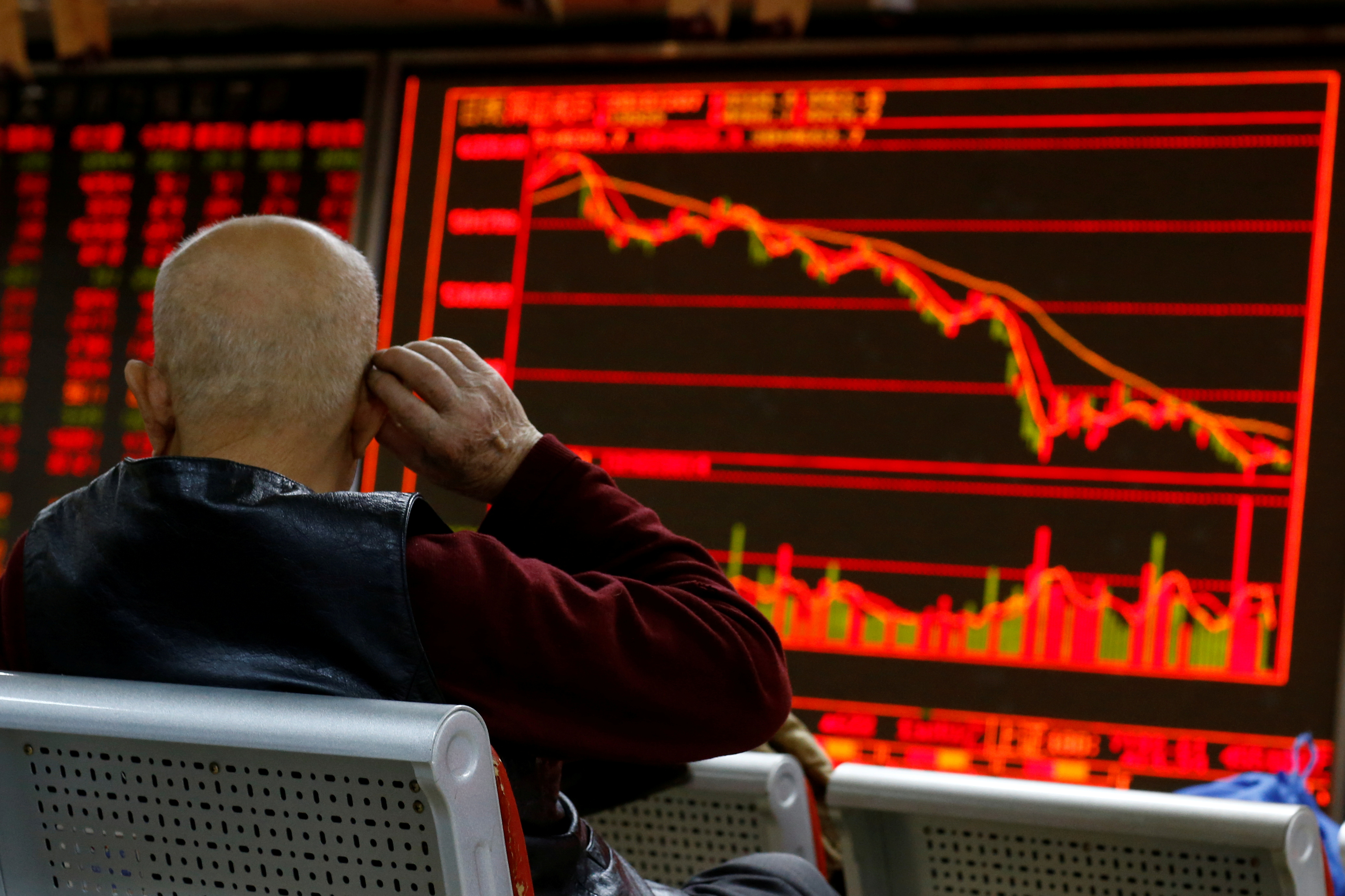 An investor sits in front of a board showing stock information at a brokerage office in Beijing, China, December 7, 2018.  REUTERS/Thomas Peter/File Photo
