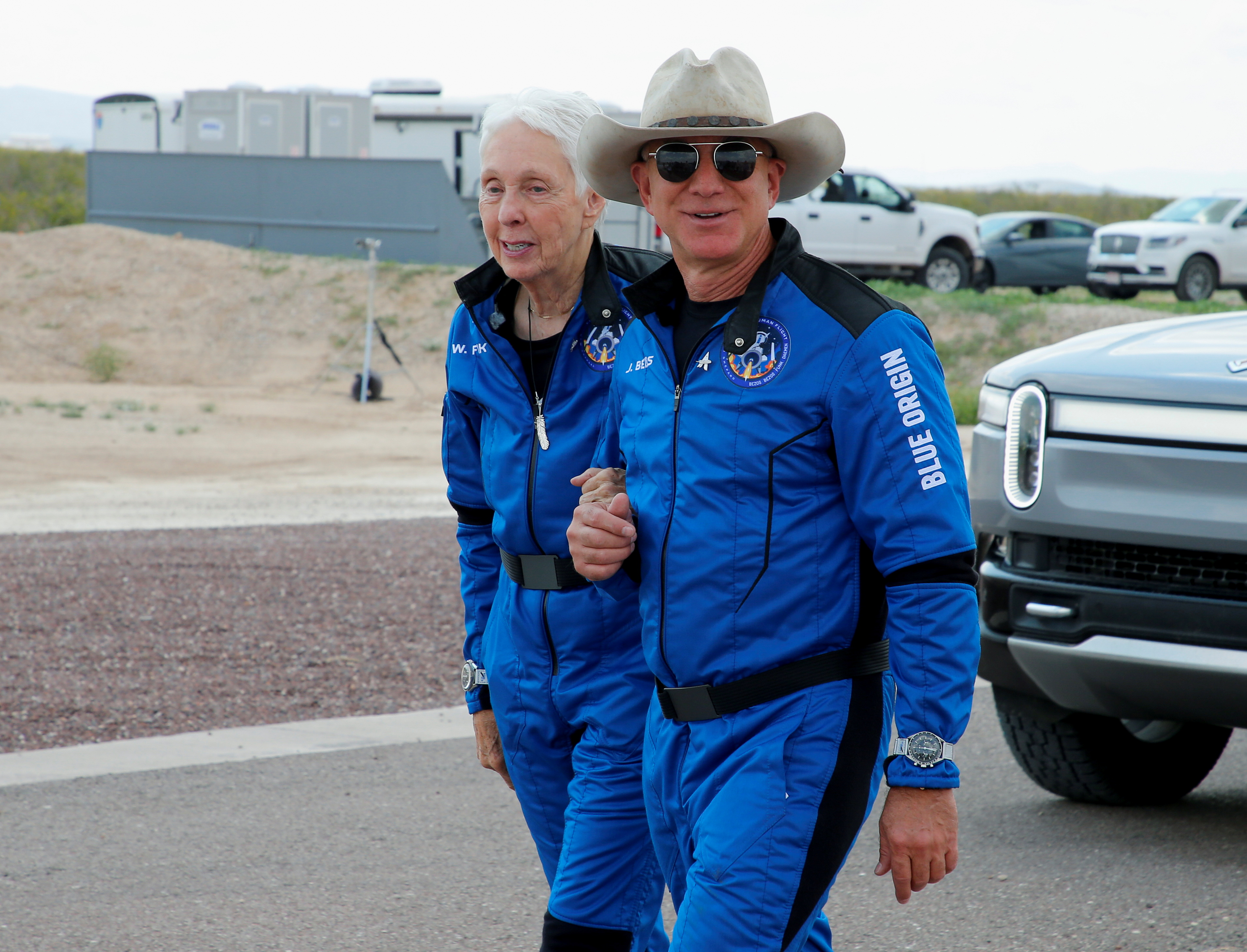 Billionaire American businessman Jeff Bezos walks with crew mate Wally Funk at the landing pad after they flew on Blue Origin's inaugural flight to the edge of space, in the nearby town of Van Horn, Texas, U.S. July 20, 2021. Funk, 82, became the oldest person in space. REUTERS/Joe Skipper/File Photo