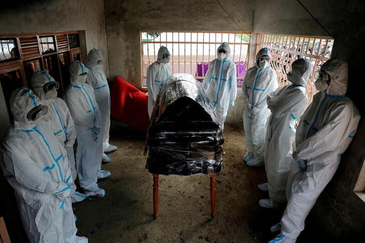 Men dressed in protective suits stand around the coffin of Kenyan doctor Daniel Alushula who died of complications related to COVID-19, at his funeral, during the coronavirus disease (COVID-19) outbreak, in the village of Khumusalaba, in Kakamega county, Kenya, November 13, 2020. REUTERS/Baz Ratner/File Photo