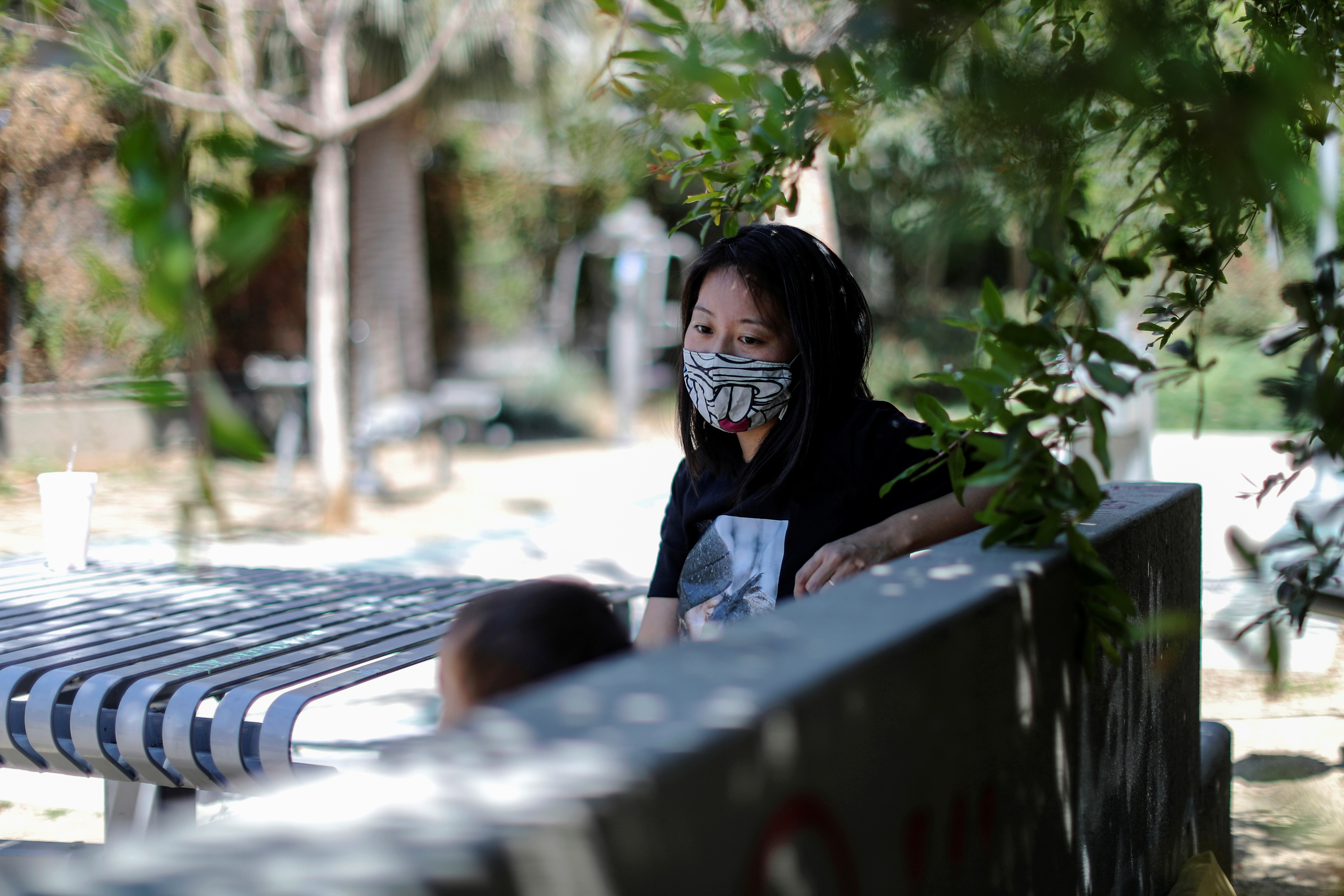Tracy Park sits in the park in which she was shouted at with her daughter, as the coronavirus disease (COVID-19) pandemic continues, in Hollywood, Los Angeles, California, U.S., April 27, 2021. PIcture taken April 27, 2021. REUTERS/Lucy Nicholson