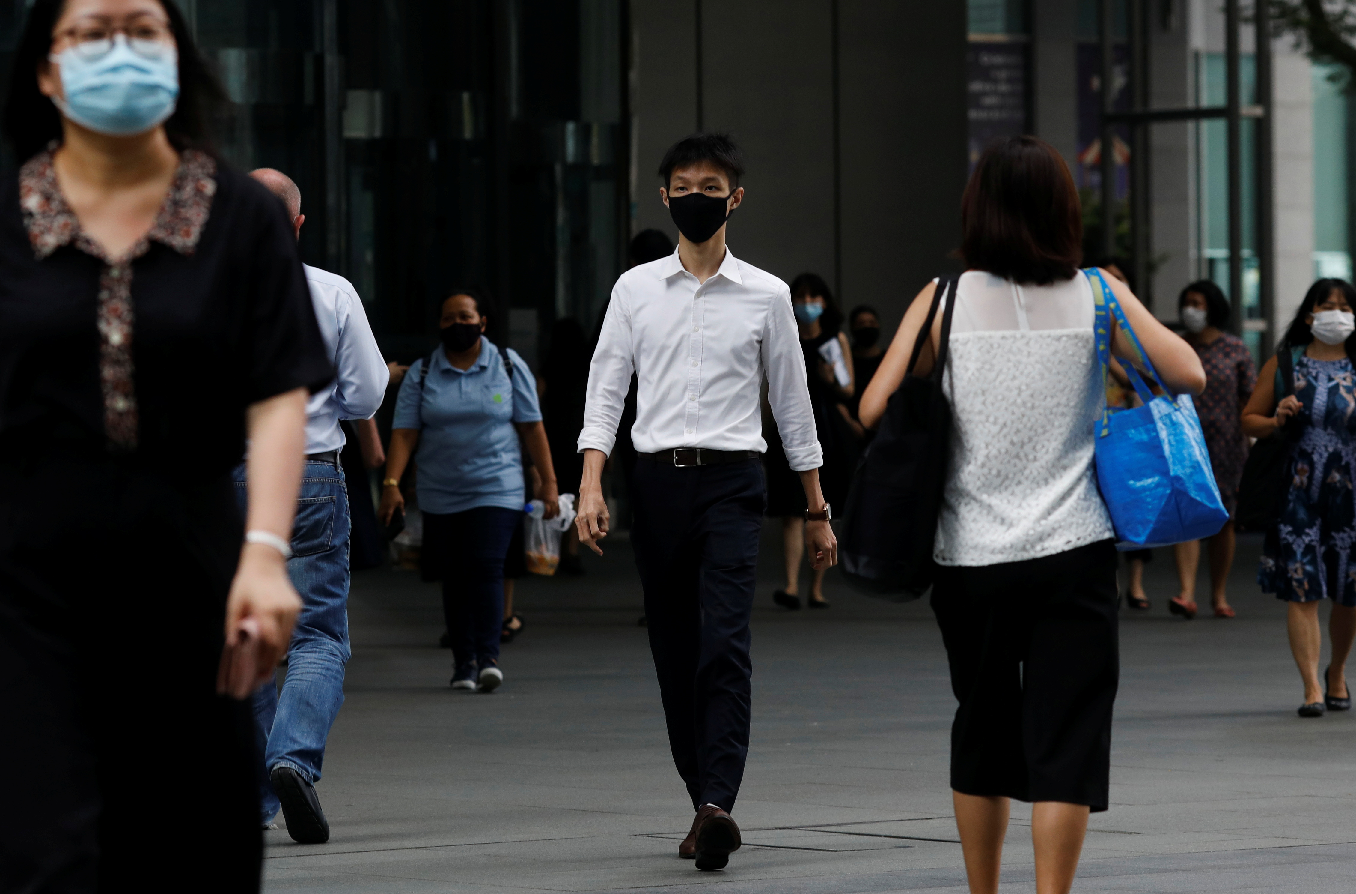 People wearing protective masks as a precaution against the coronavirus disease (COVID-19) walk during lunch hour at the central business district in Singapore, December 14, 2020.  REUTERS/Edgar Su