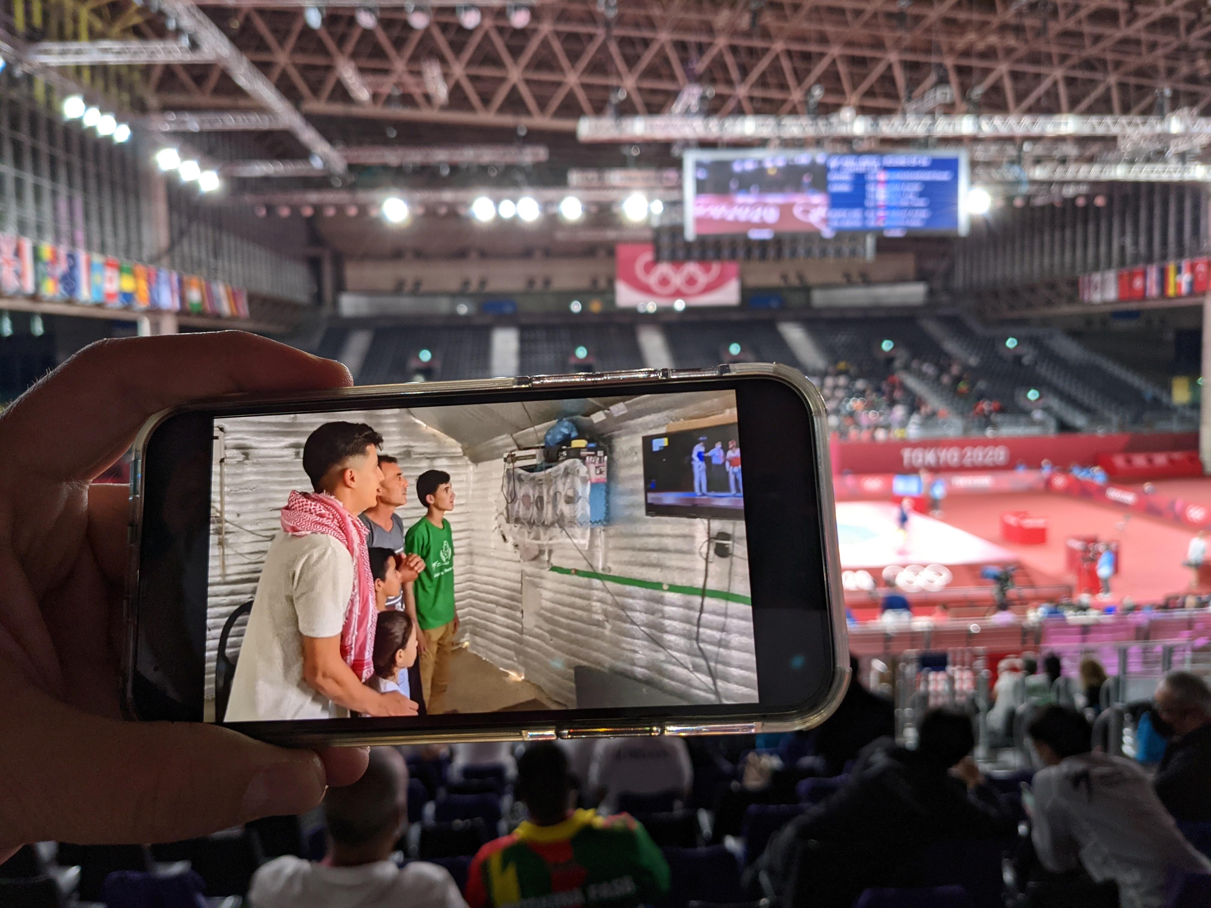 A World Taekwondo official shows a video of Syrian refugee Wael Al Faraj watching a taekwondo match on TV from Jordan's Azraq refugee camp, at an Olympic venue in Chiba, Japan, July 26, 2021. REUTERS/Chang-Ran Kim