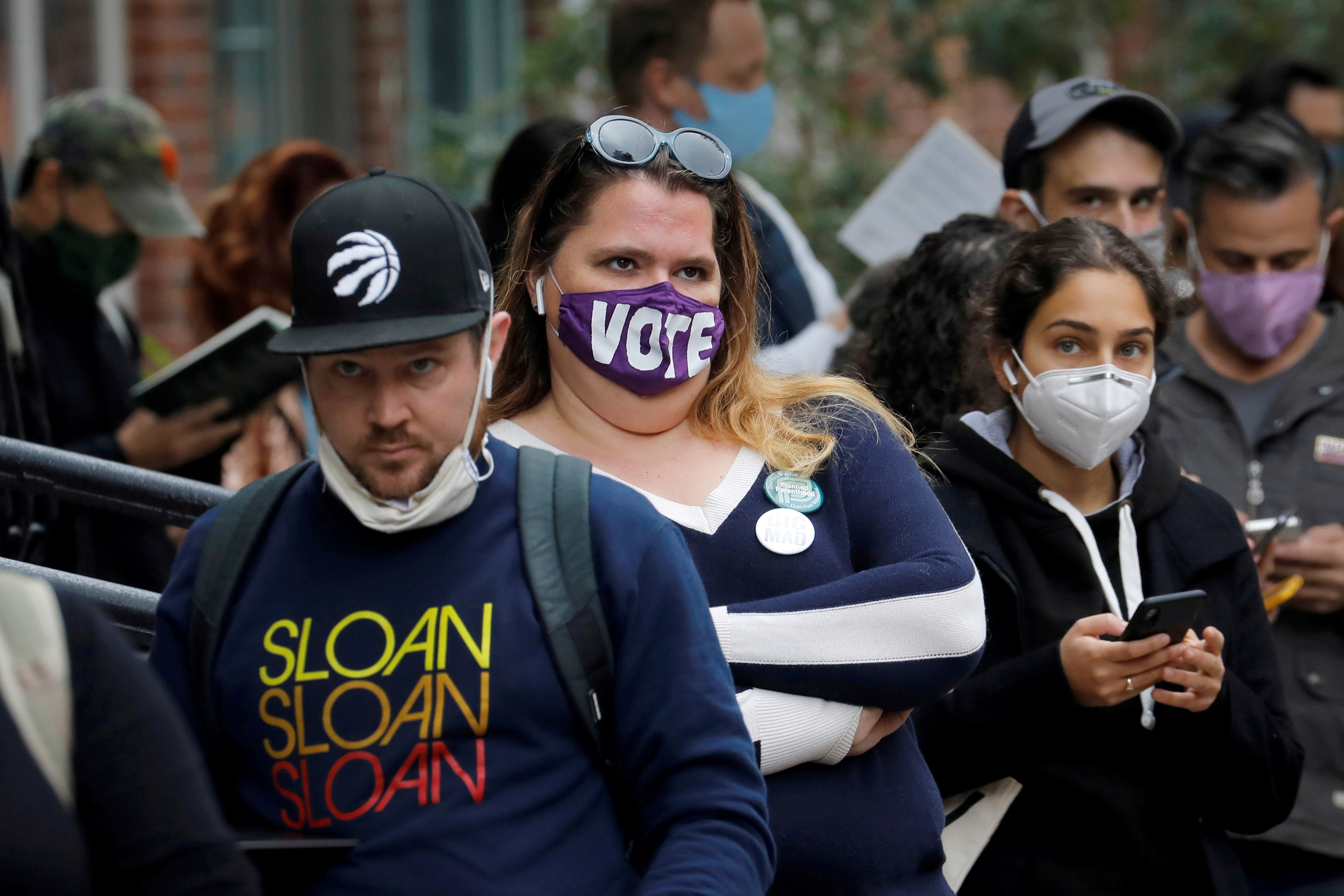 Voters wait in line for hours, including some who received sandwiches from volunteers in Brooklyn, to cast their ballots during early voting in the Brooklyn borough of New York City, New York, U.S., October 27, 2020. REUTERS/Mike Segar/File Photo