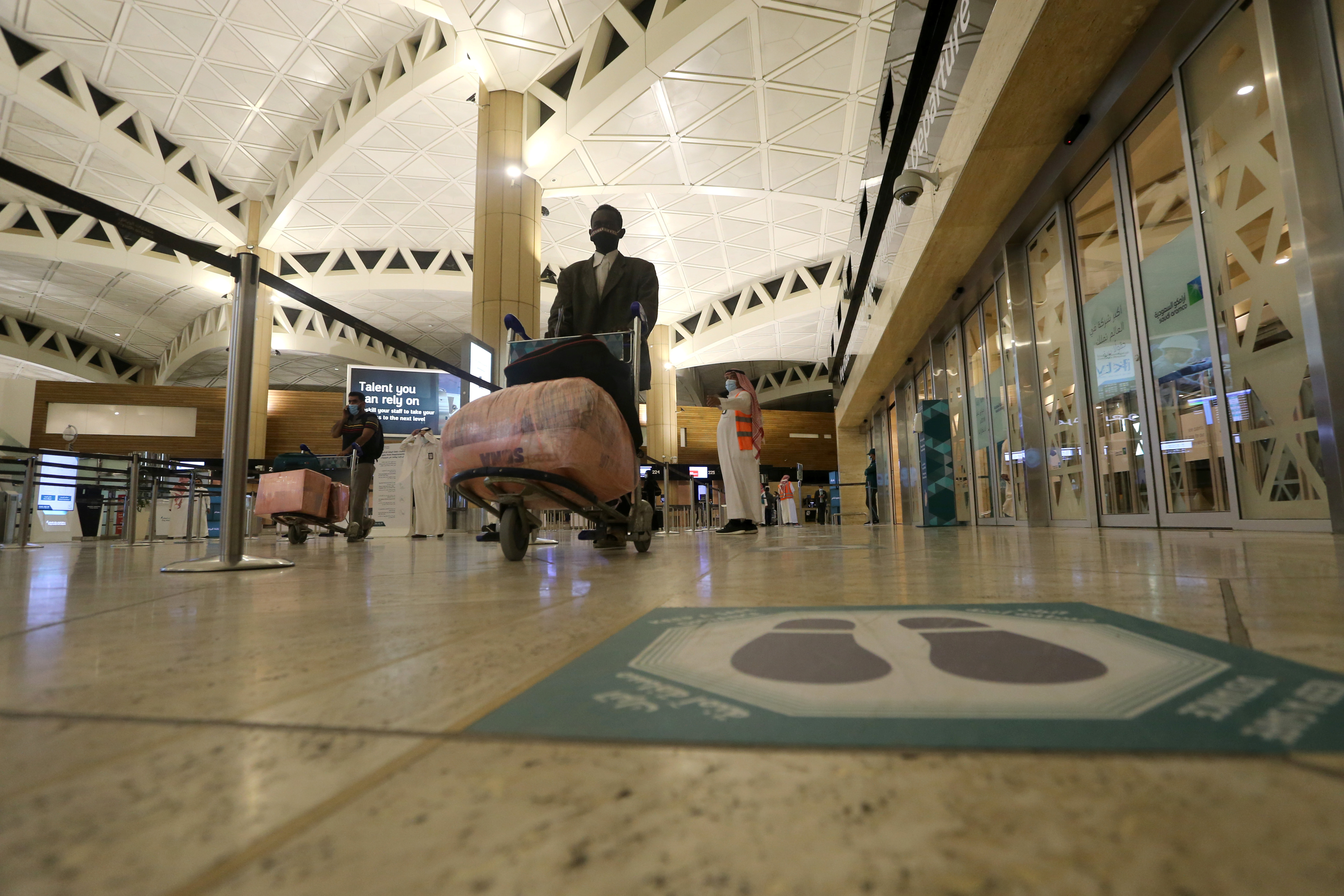A social distancing sign is seen on the floor as a Saudi man man wearing a face mask walks with his luggage at the King Khalid International Airport, after Saudi authorities lifted the travel ban on its citizens after fourteen months due to coronavirus disease (COVID-19) restrictions, in Riyadh, Saudi Arabia, May 16, 2021. REUTERS/Ahmed Yosri