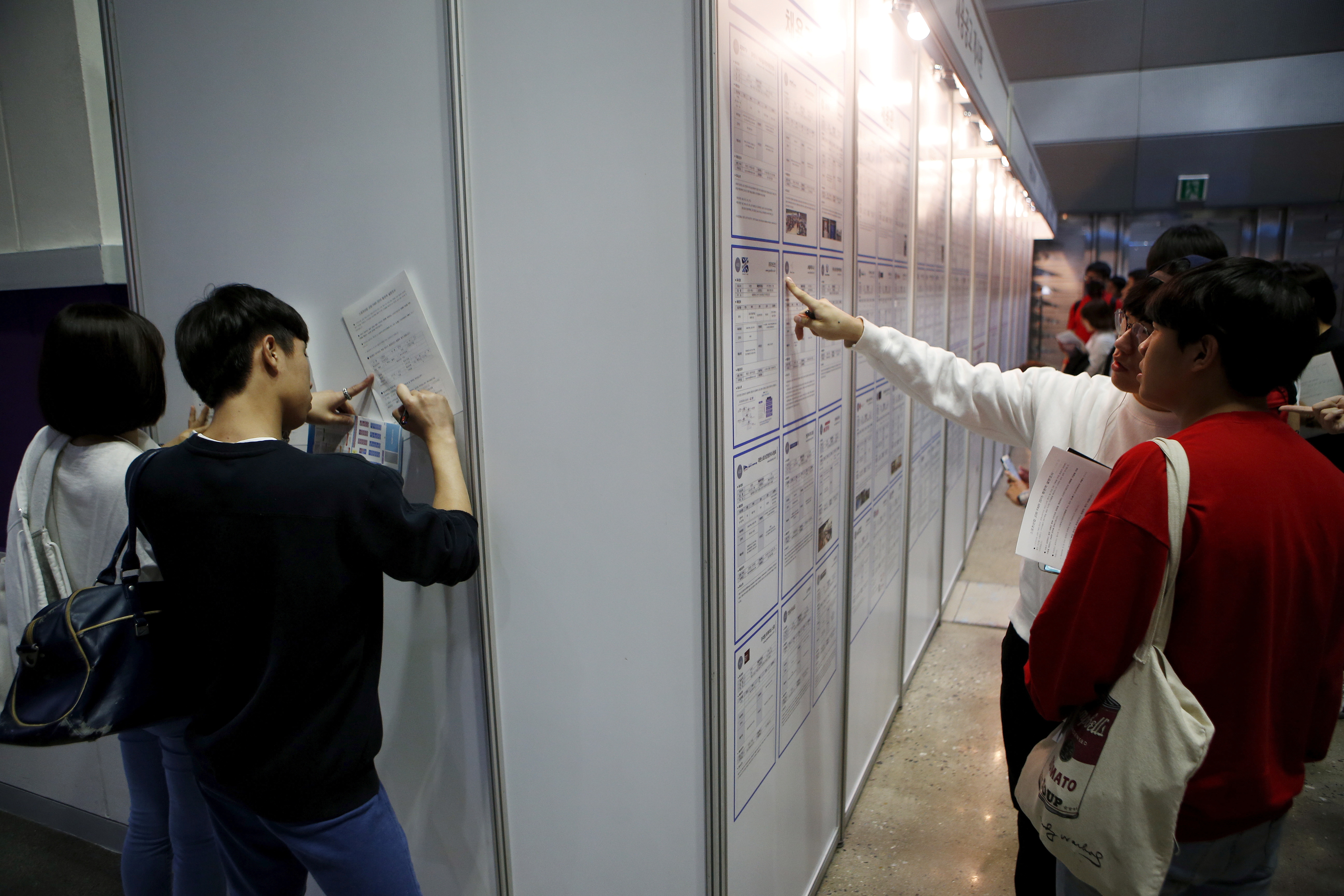 University students (R) look at recruiting information as others write on documents at an employment fair in Seoul, South Korea, September 23, 2015. REUTERS/Kim Hong-Ji/File Photo