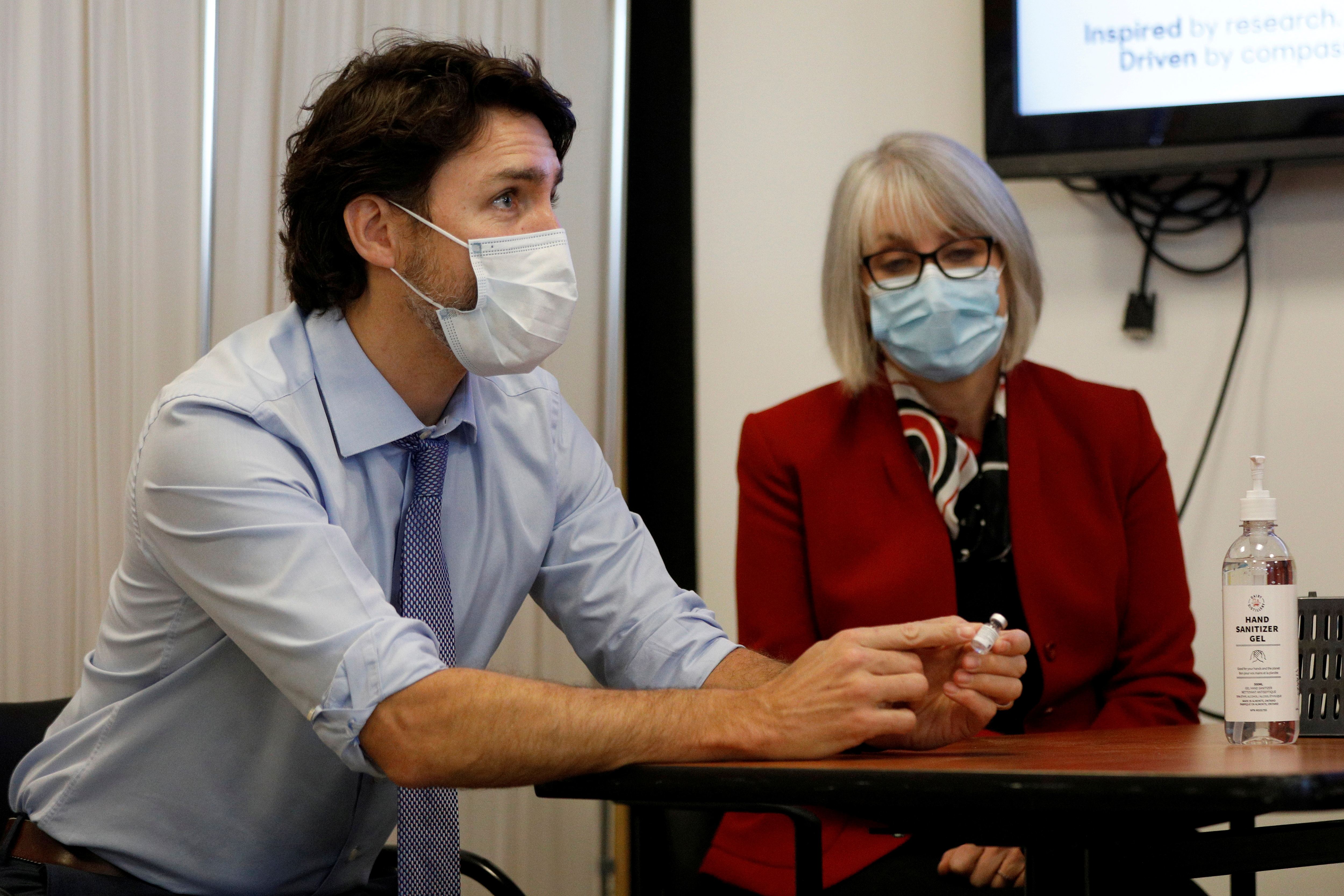 Canada's Prime Minister Justin Trudeau, with Minister of Health Patty Hajdu, holds an empty COVID-19 vaccine vial after the first vaccinations were given at the Civic Hospital in Ottawa, Ontario, Canada December 15, 2020. REUTERS/Blair Gable/File Photo