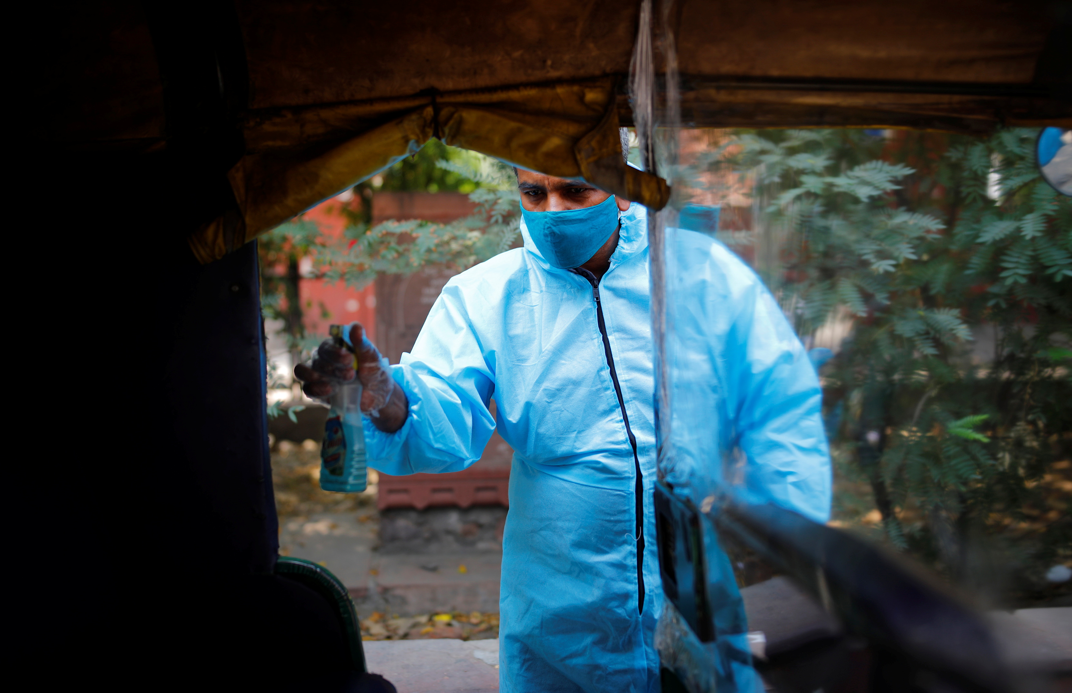 Raj Kumar, 42, a driver of an auto rickshaw ambulance which is prepared to transfer people suffering from the coronavirus disease (COVID-19) and their relatives for free, sanitizes his vehicle in New Delhi, India May 6, 2021. REUTERS/Adnan Abidi