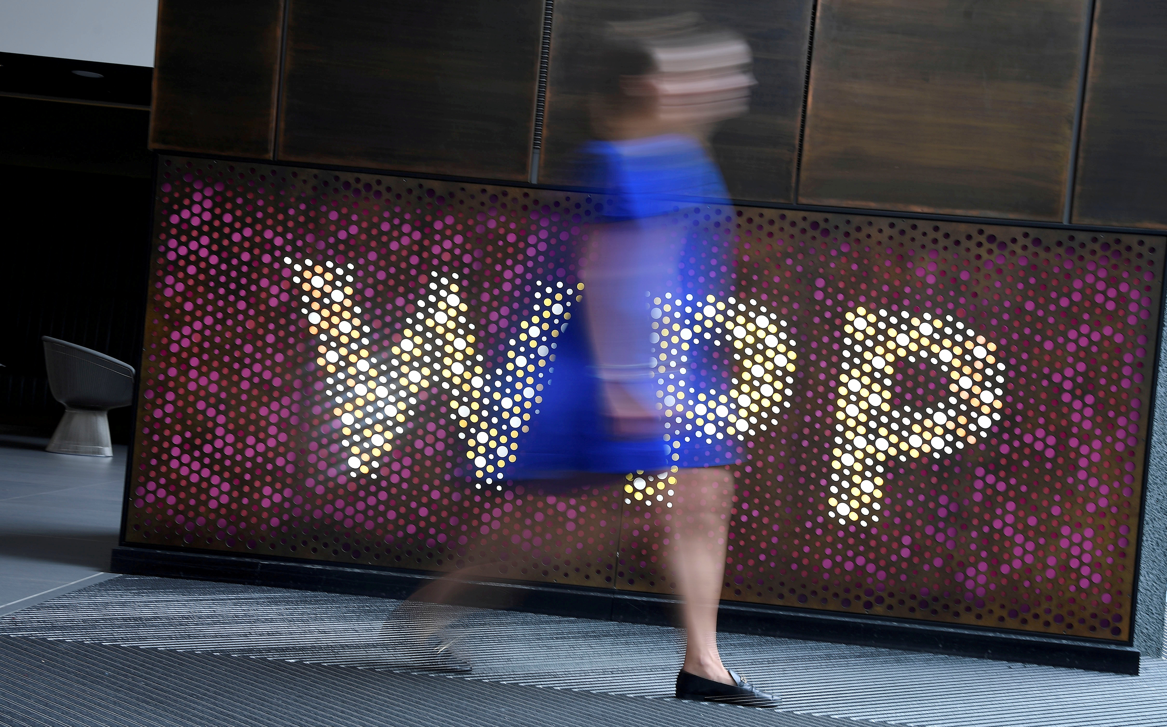 A woman walks past signage for WPP at their offices in London, Britain, July 17, 2019. REUTERS/Toby Melville