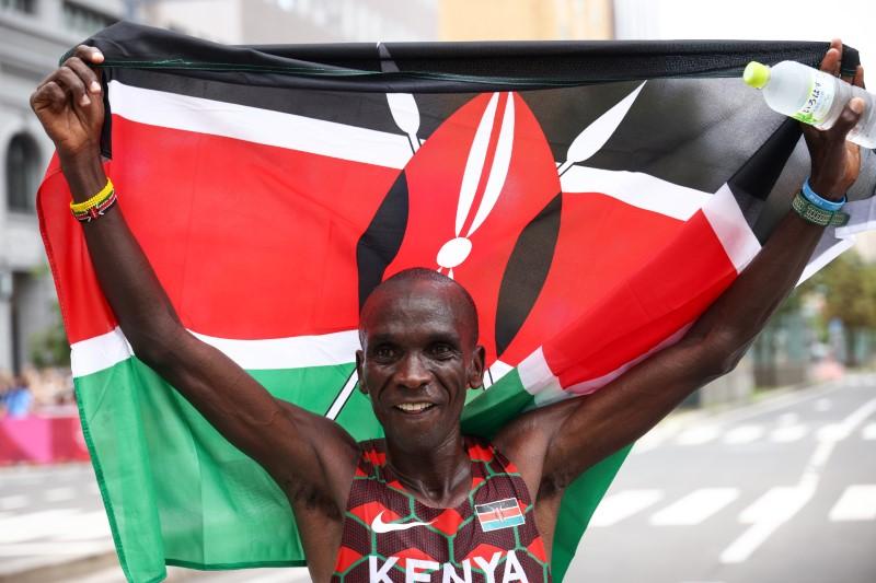 Tokyo 2020 Olympics - Athletics - Men's Marathon - Sapporo Odori Park, Sapporo, Japan - August 8, 2021. Eliud Kipchoge of Kenya holds the flag of Kenya and celebrates after winning gold REUTERS/Kim Hong-Ji