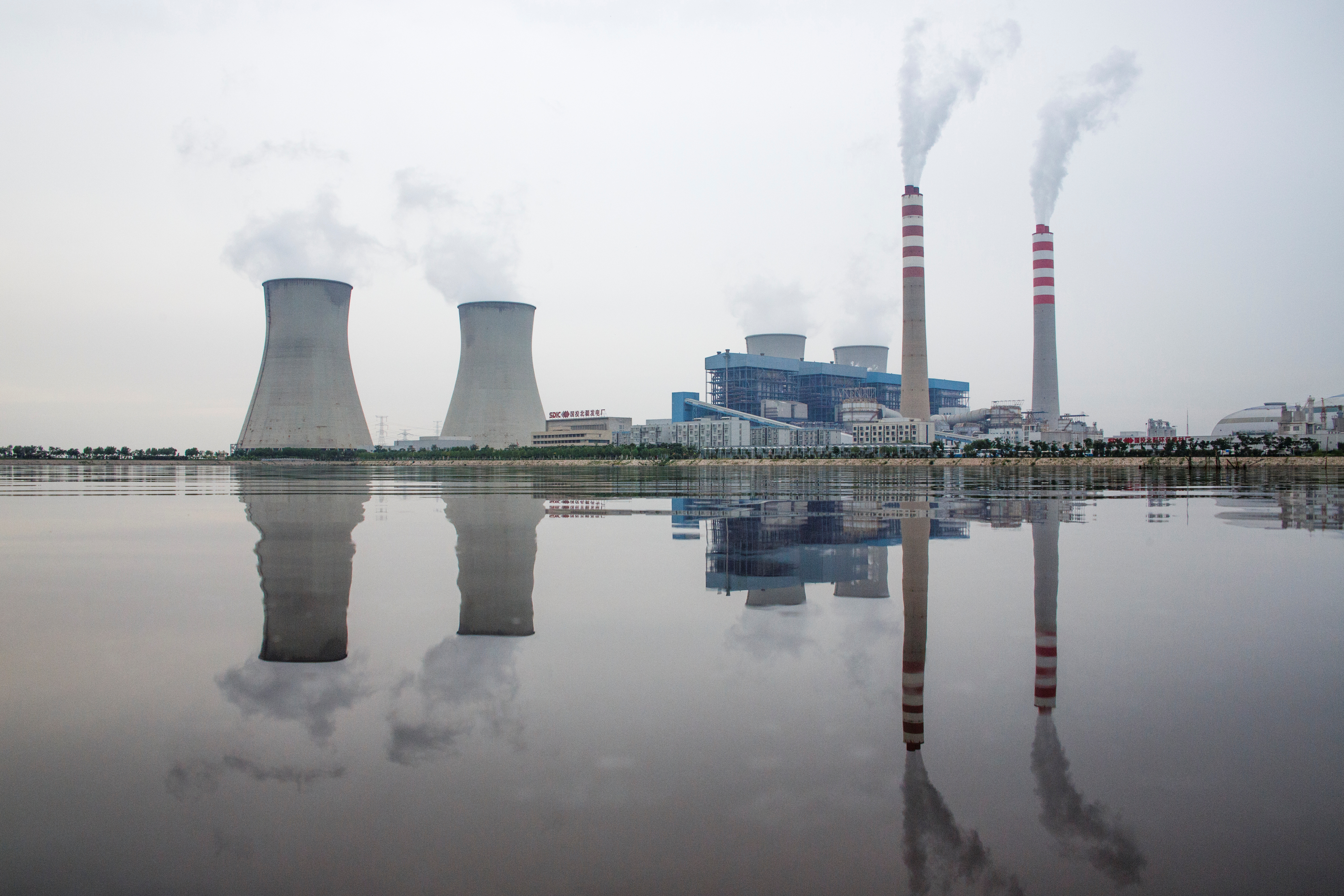 A power station of the State Development & Investment Corporation (SDIC) is reflected in a lake in Tangshan, Hebei province, China, August 22, 2018.  REUTERS/Thomas Peter