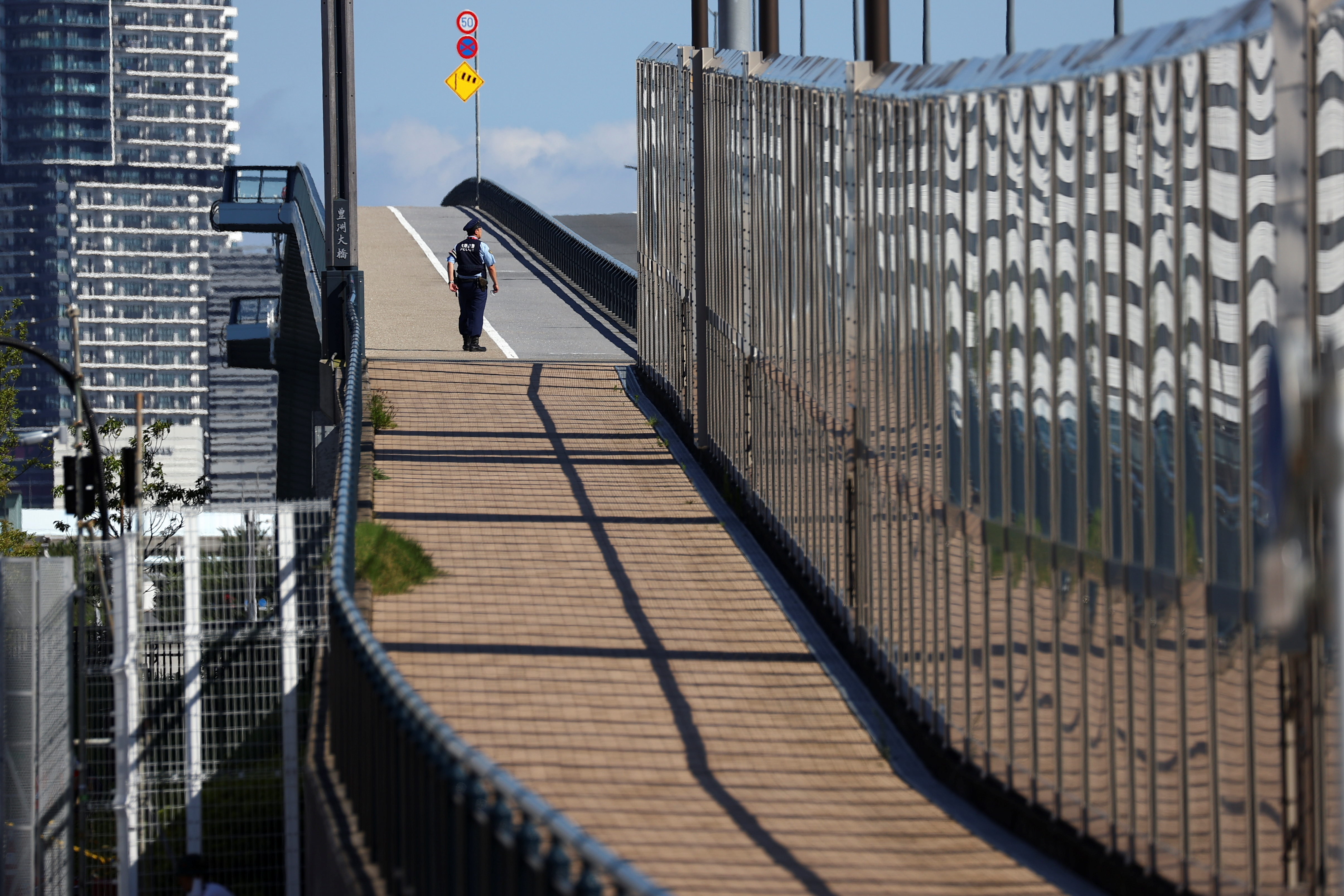 A police officer patrols around, outside the Athletes Village, where a person has tested positive for COVID-19, ahead of Tokyo 2020 Olympic Games in Tokyo, Japan July 17,  2021. REUTERS/Kim Kyung-Hoon
