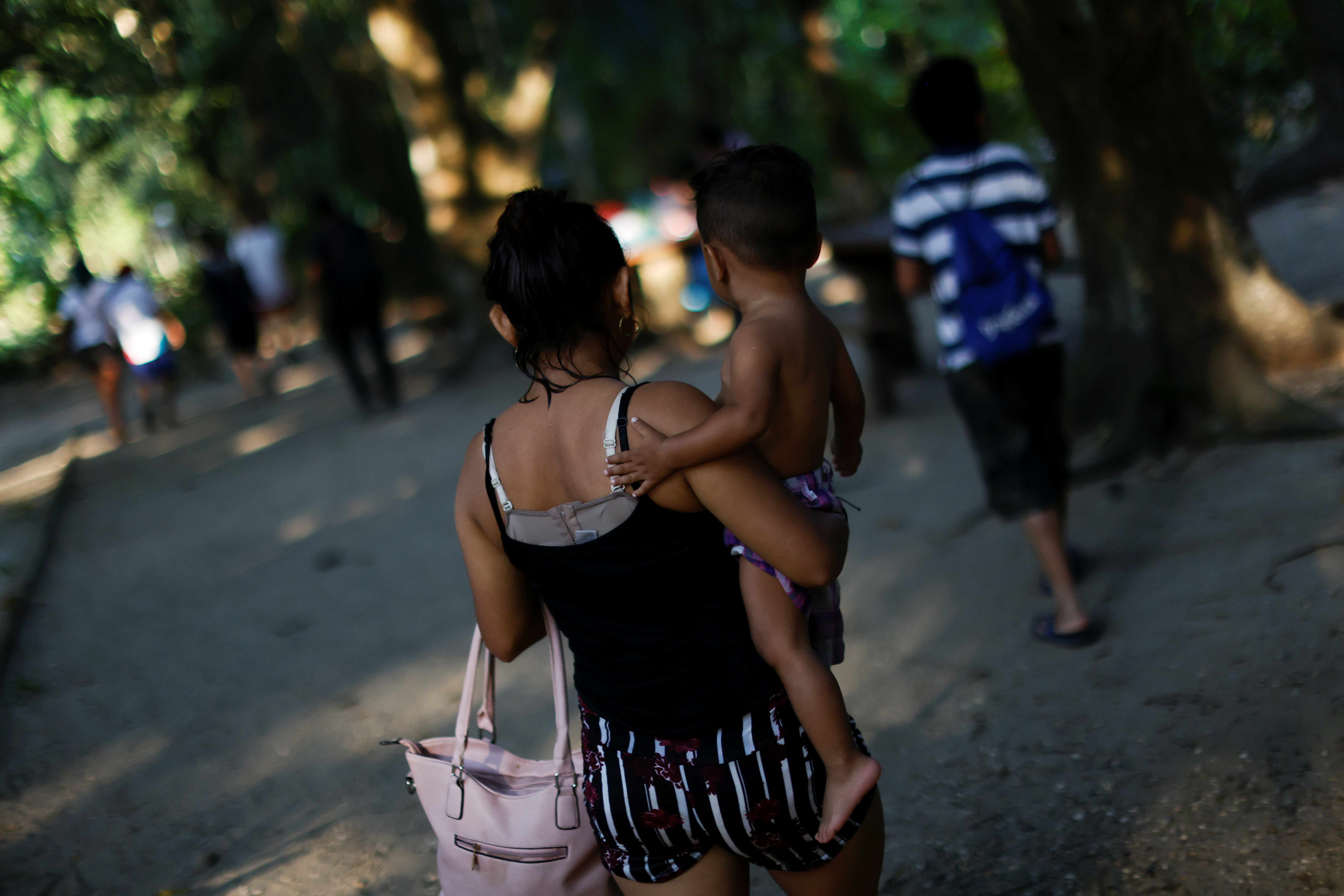 A young mother from Honduras, who is living in La 72 migrant shelter, is seen on a day out at the river in Tenosique, Tabasco,  Mexico March 26, 2021. Picture taken March 26, 2021.REUTERS/Carlos Jasso