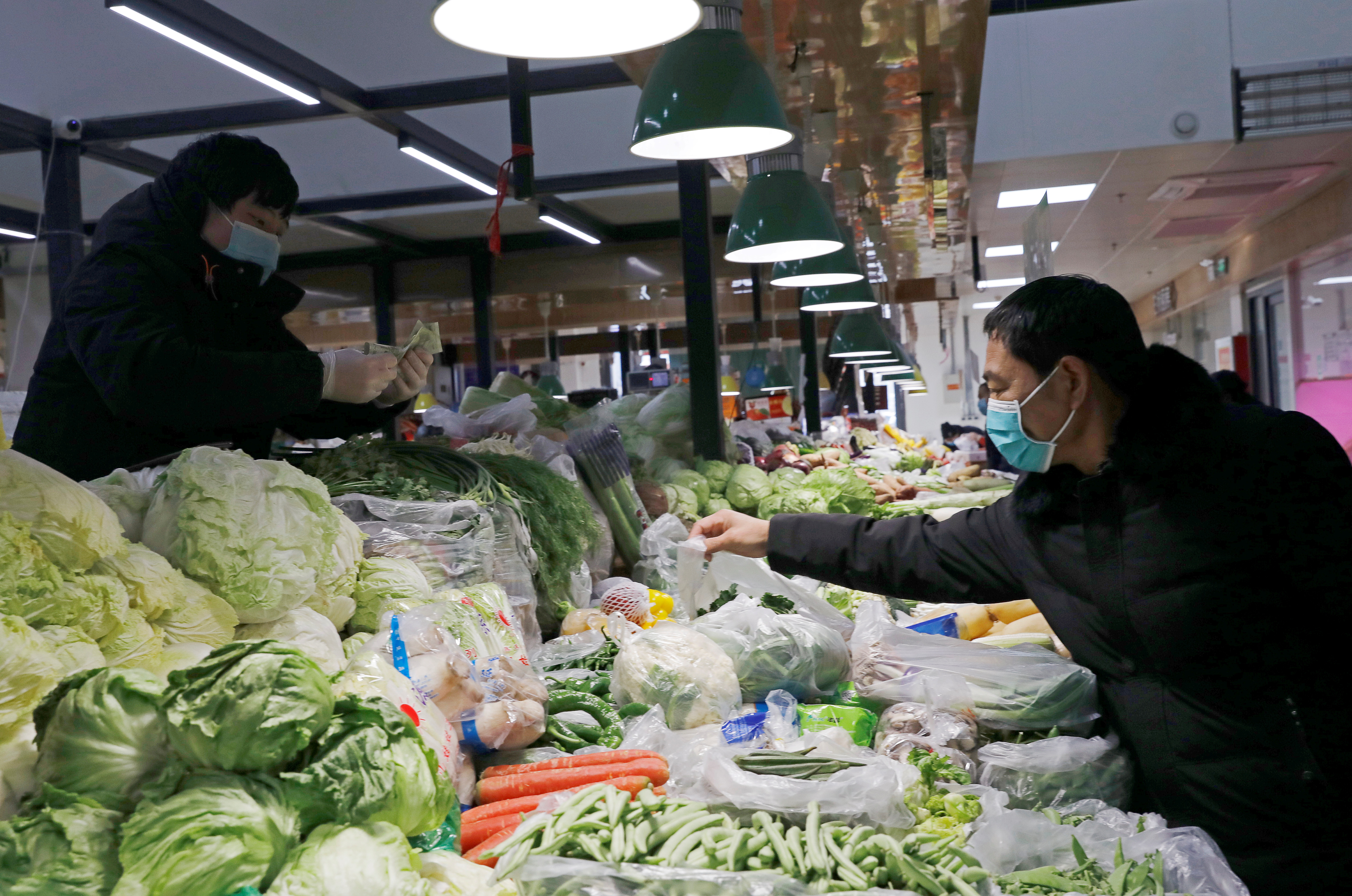 People wearing face masks shop at a market, following new cases of the coronavirus disease (COVID-19) in the country, in Beijing, China January 11, 2021. REUTERS/Tingshu Wang
