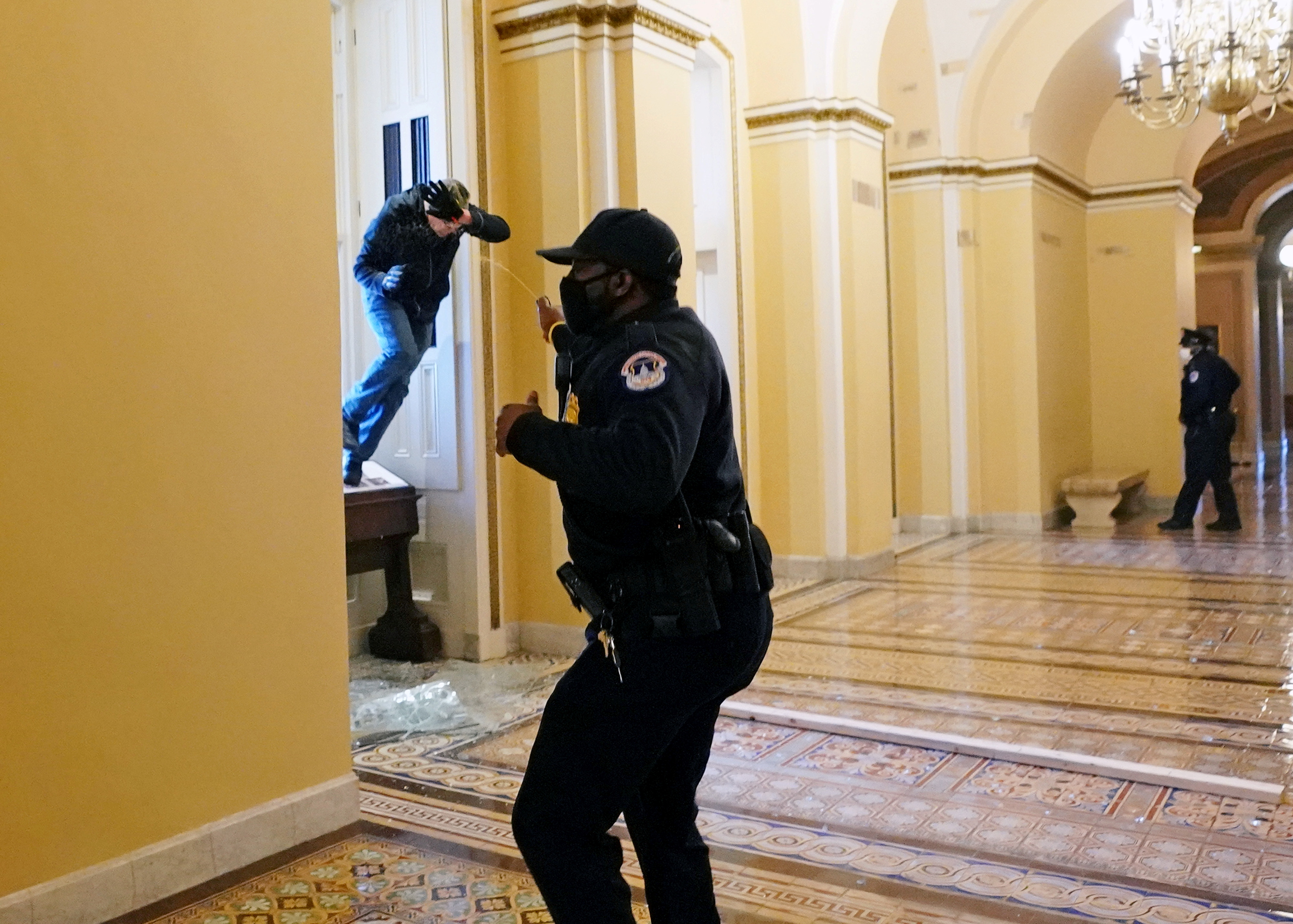 A U.S. Capitol police officer shoots pepper spray at a protestor attempting to enter the Capitol building during a joint session of Congress to certify the 2020 election results on Capitol Hill in Washington, U.S., January 6, 2021.  Kevin Dietsch/Pool via REUTERS