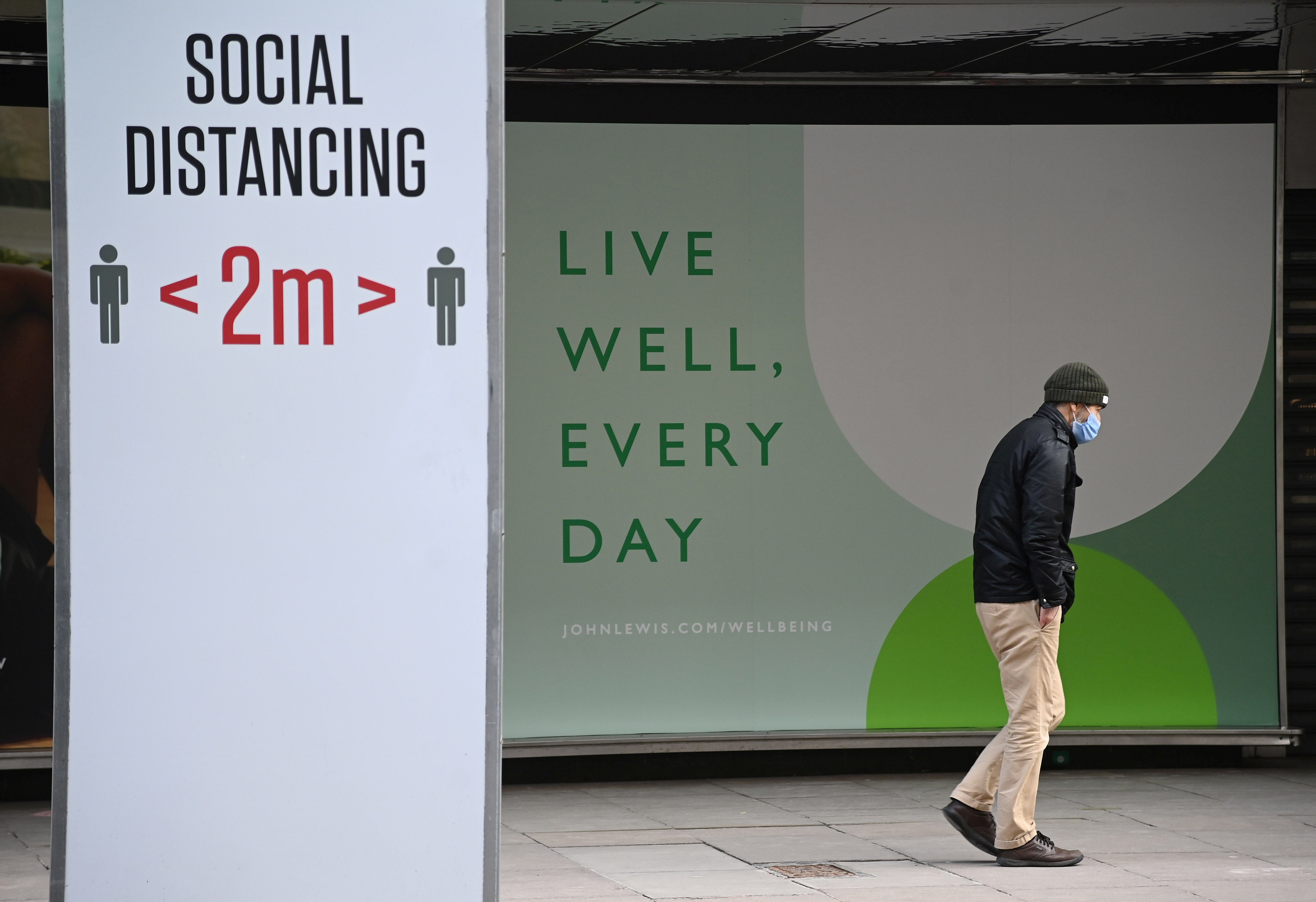 A person walks past a closed shopfront on Oxford Street, as official figures are published for UK GDP in 2020, London, Britain, February 12, 2021. REUTERS/Toby Melville