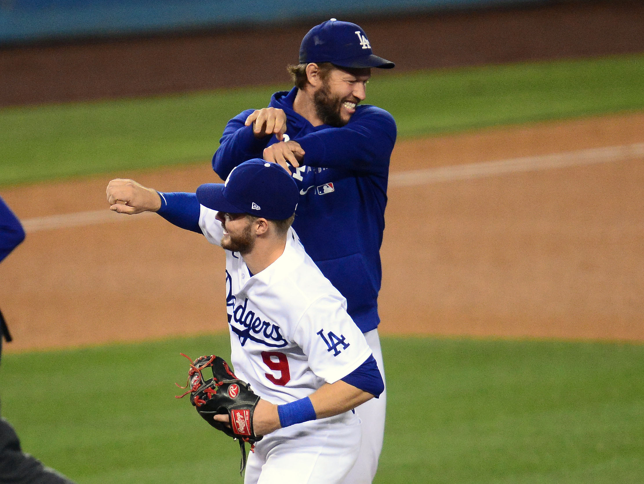 May 11, 2021; Los Angeles, California, USA; Los Angeles Dodgers starting pitcher Clayton Kershaw (22) celebrates with second baseman Gavin Lux (9) the 6-4 victory against the Seattle Mariners at Dodger Stadium. Mandatory Credit: Gary A. Vasquez-USA TODAY Sports