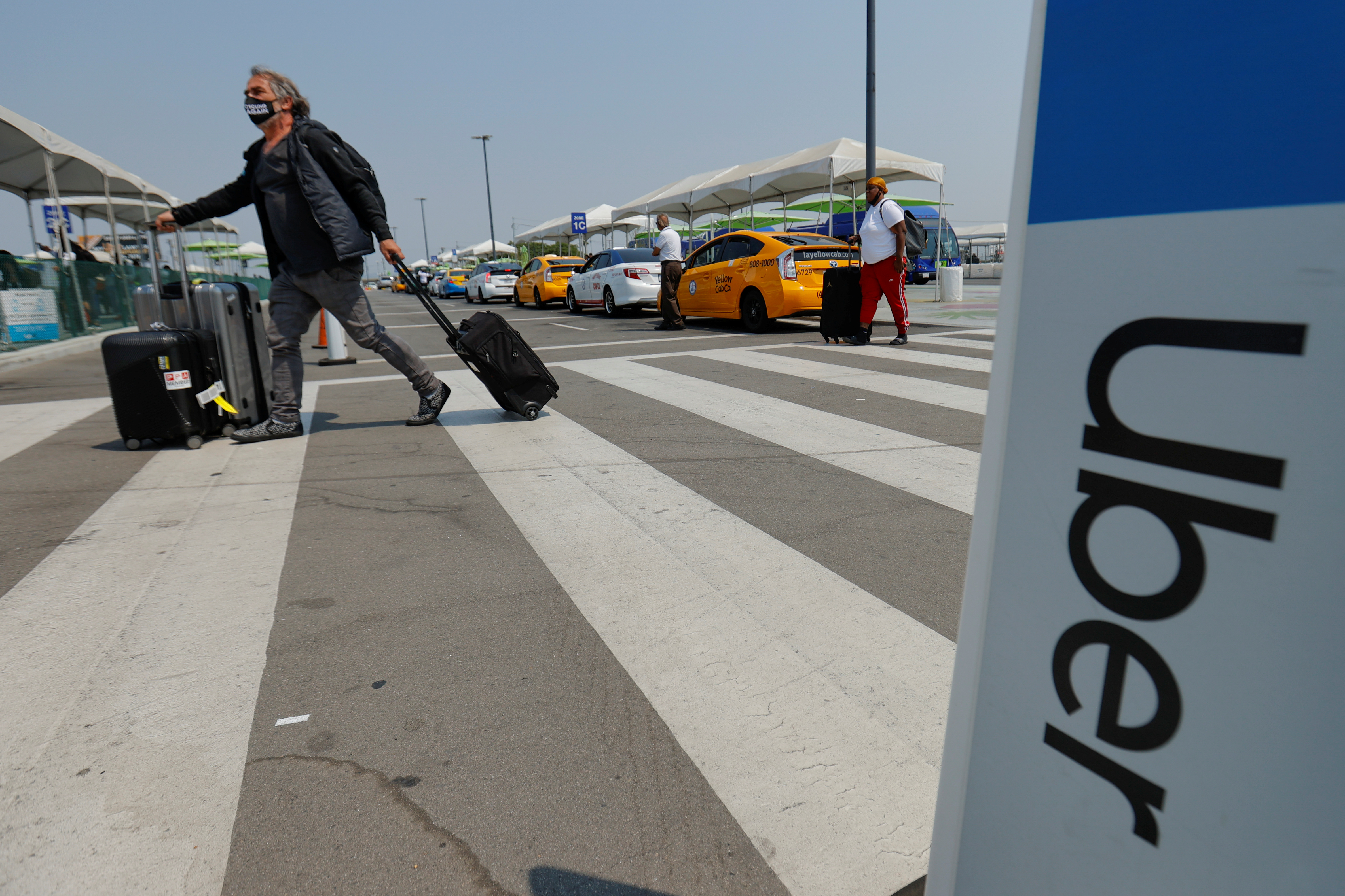 Travelers arriving at Los Angeles International Airport look for ground transportation  in Los Angeles, Aug. 20, 2020. REUTERS/Mike Blake