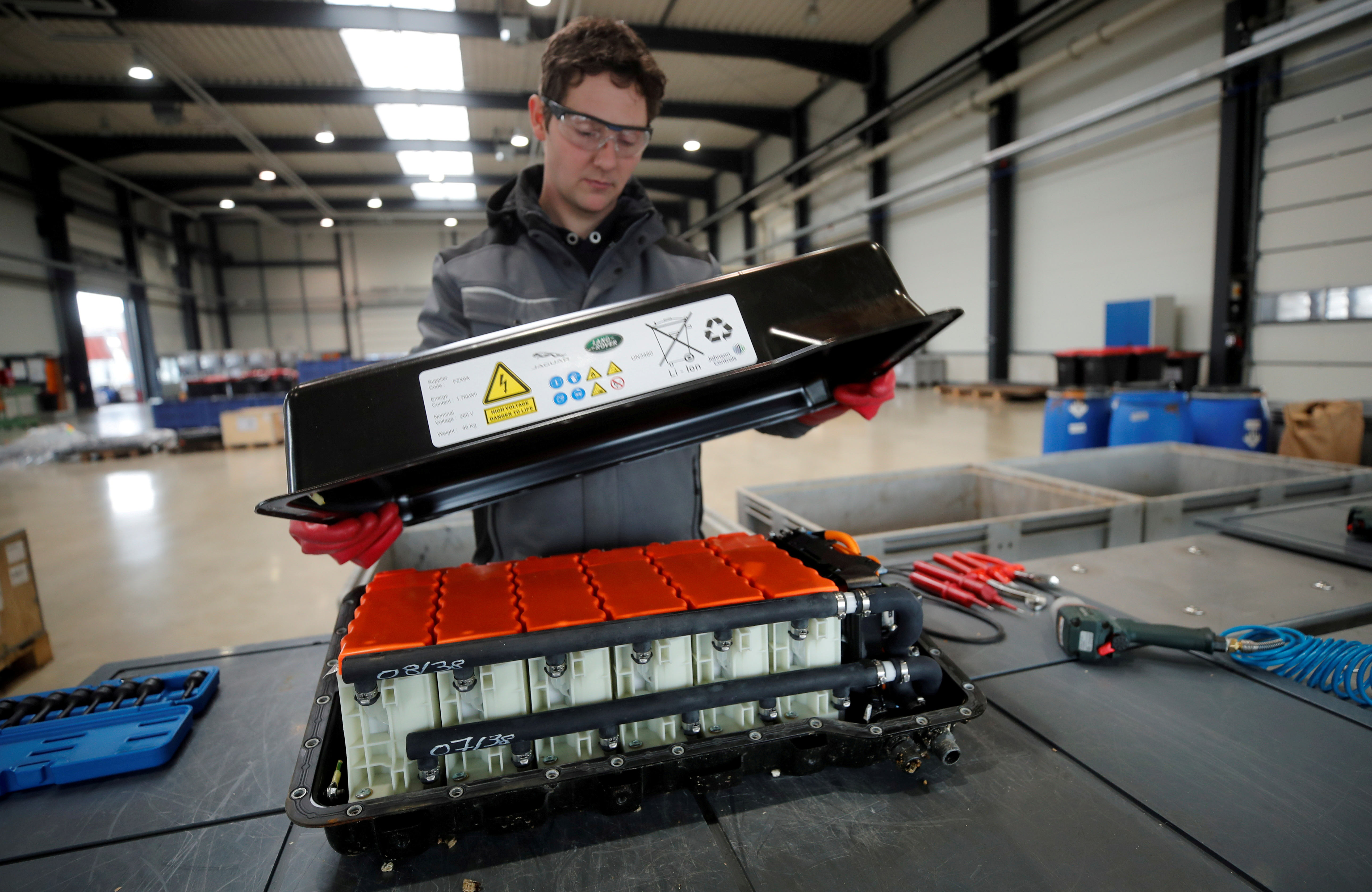 A used Lithium-ion car battery is opened before its dismantling by an employee of the German recycling firm Accurec in Krefeld, Germany, November 16, 2017. Picture taken November 16, 2017. REUTERS/Wolfgang Rattay