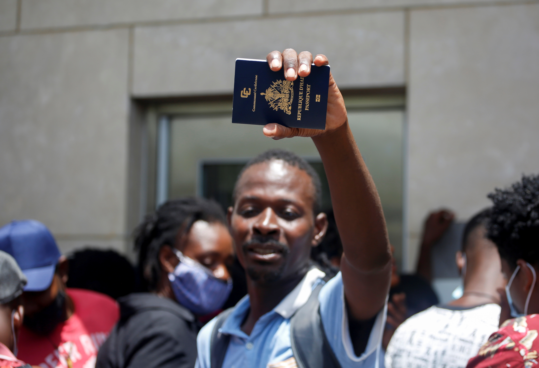 Un hombre haitiano muestra su pasaporte frente a la embajada de los Estados Unidos después del asesinato del presidente Jovenel Moise, en Puerto Príncipe, Haití, el 9 de julio de 2021. REUTERS / Estailove St-Val