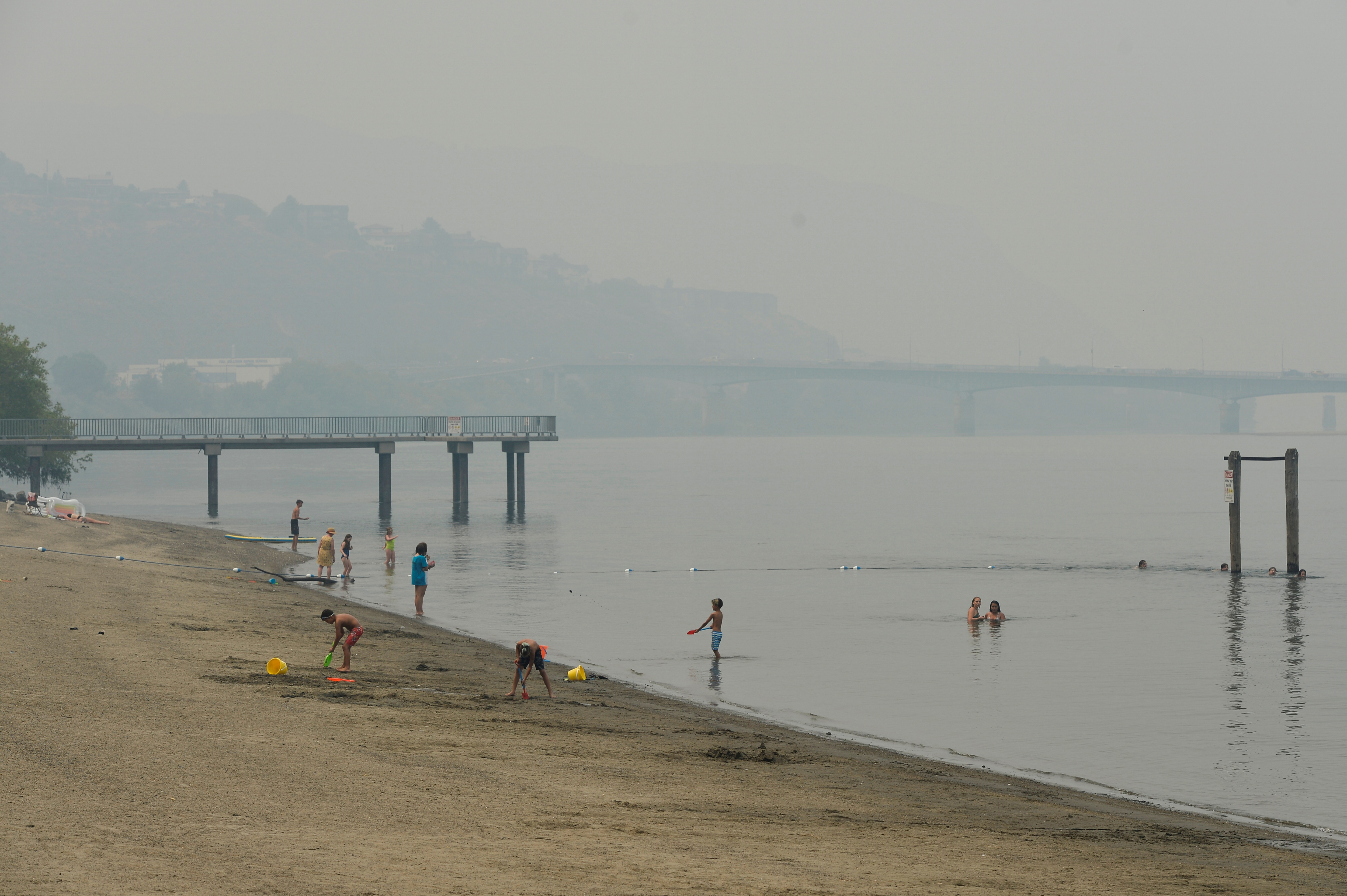 Swimmers cool off in the Thompson River under a blanket of smoke from nearby wildfires in Kamloops, British Columbia, Canada July 15, 2021.  REUTERS/Jennifer Gauthier/File Photo