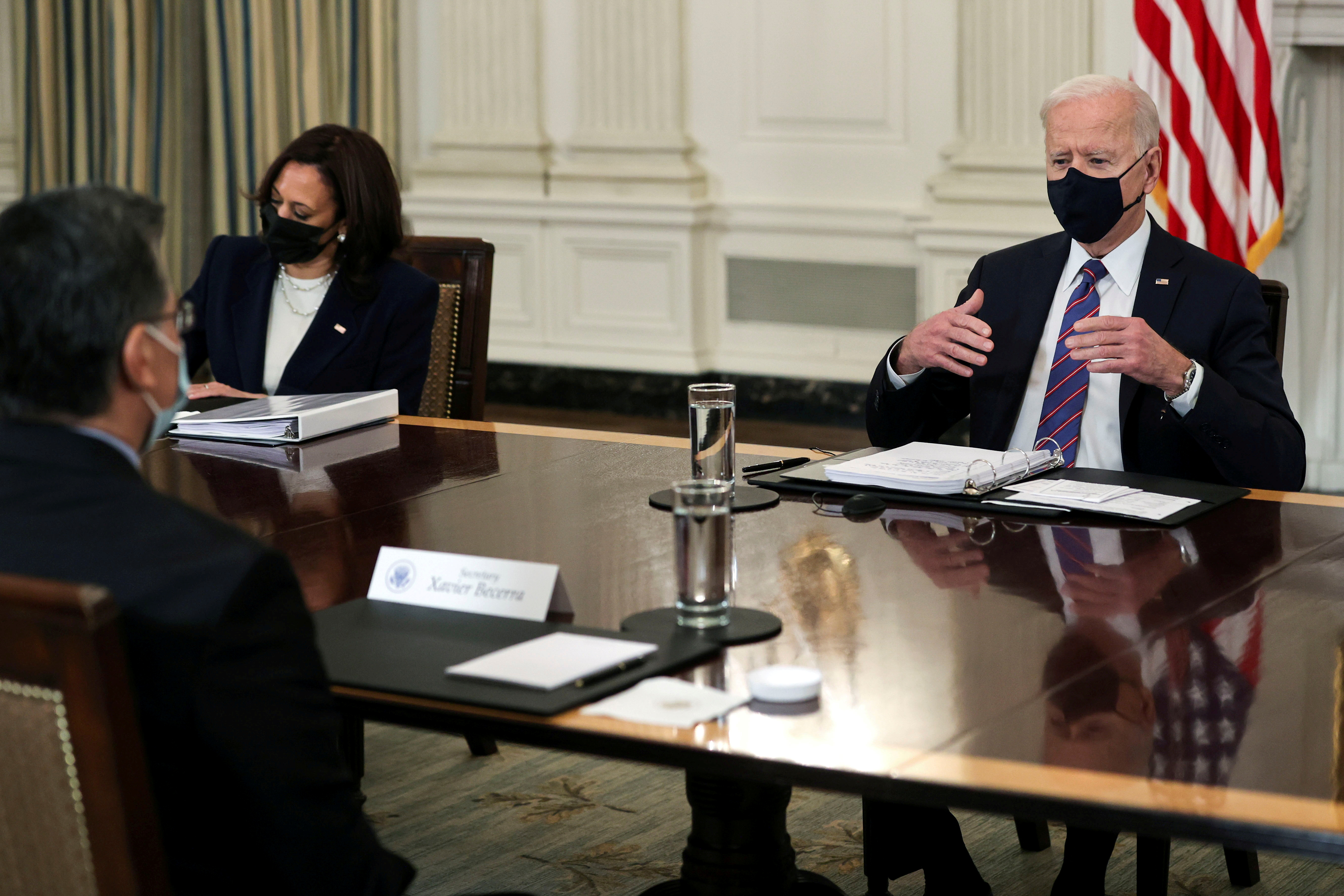 U.S. President Joe Biden is flanked by Vice President Kamala Harris as he speaks with HHS Secretary Xavier Becerra during a meeting with immigration advisers in the State Dining Room at the White House in Washington, U.S., March 24, 2021. REUTERS/Jonathan Ernst/File Photo