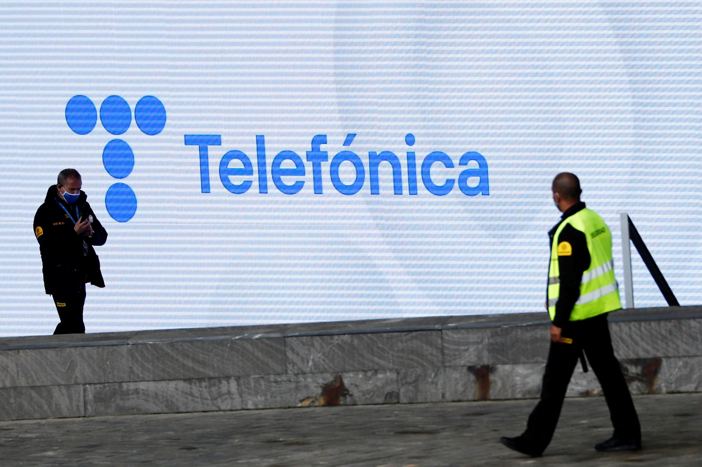 Security guards walk past a screen displaying the logo of Spanish company Telefonica at its headquarters in Madrid, Spain, May 12, 2021. REUTERS/Sergio Perez/File Photo