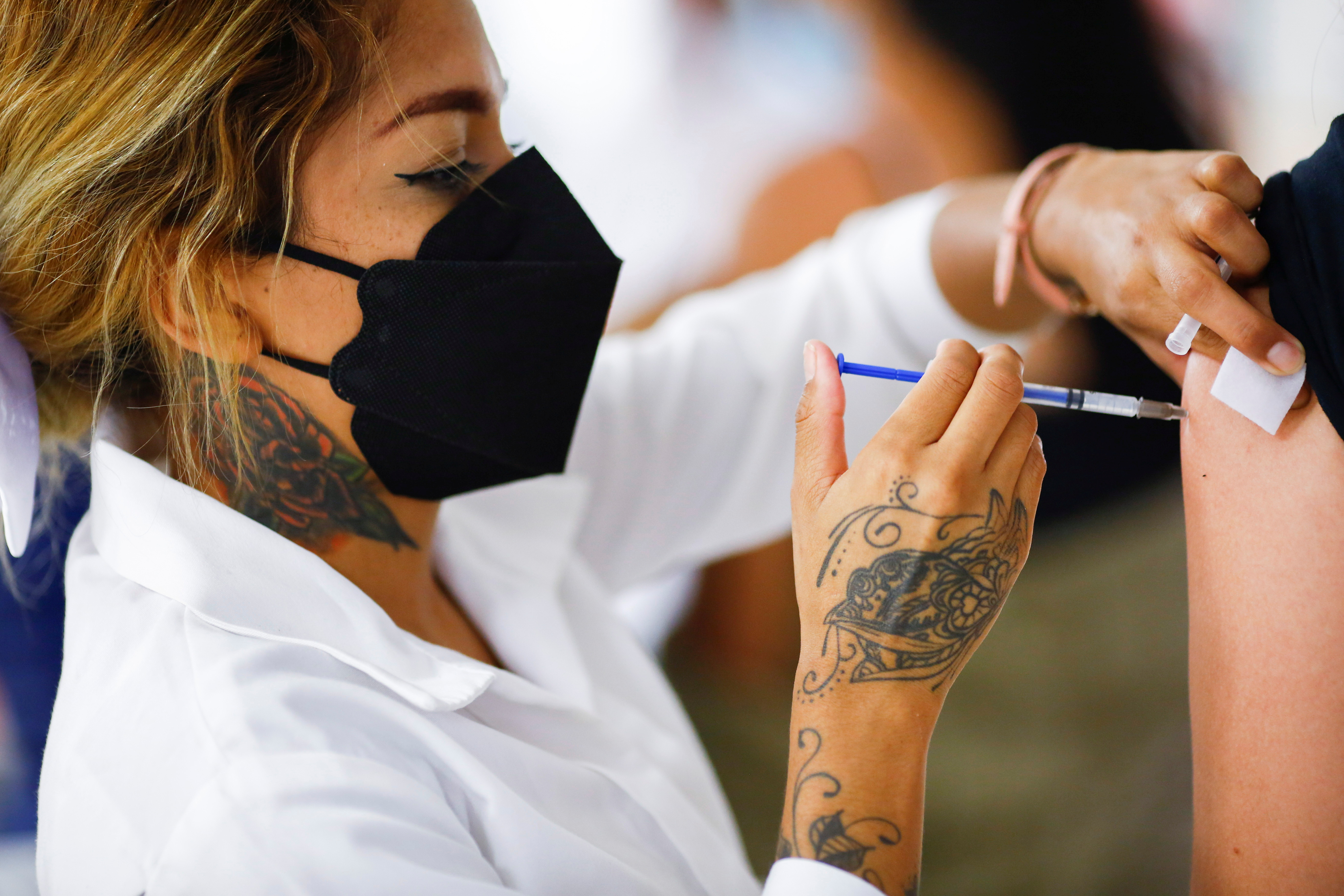 Ely Herrera, a health worker, injects a dose of the Pfizer-BioNTech coronavirus disease (COVID-19) vaccine during a mass vaccination program at Lear Corporation in Ciudad Juarez, Mexico August 24, 2021. REUTERS/Jose Luis Gonzalez