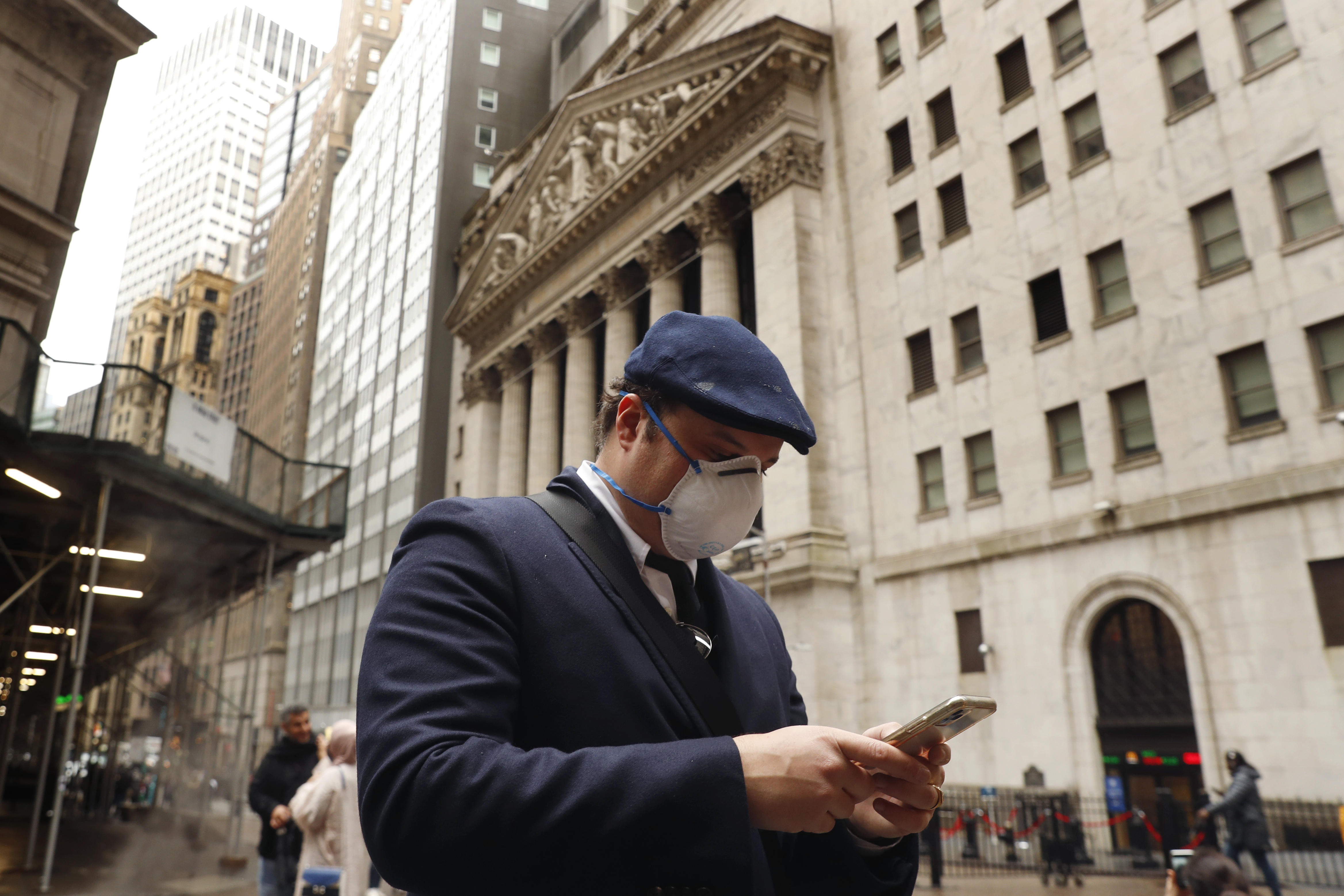 A man wears a protective mask as he walks past the New York Stock Exchange on the corner of Wall and Broad streets during the coronavirus outbreak in New York City, New York, U.S., March 13, 2020. REUTERS/Lucas Jackson