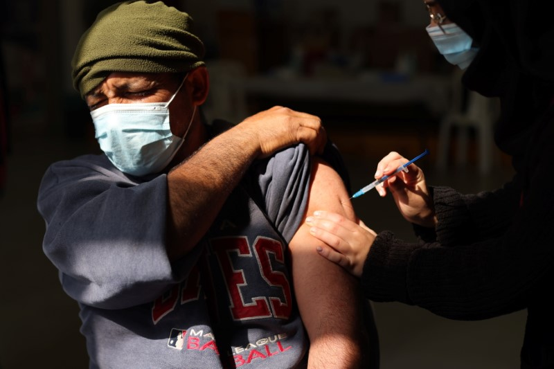 A Palestinian labourer who works within Israel or its settlements in the occupied West Bank, is vaccinated at an Israeli facility at Shaar Efraim crossing from Israel to the West Bank, March 8, 2021. REUTERS/ Ammar Awad