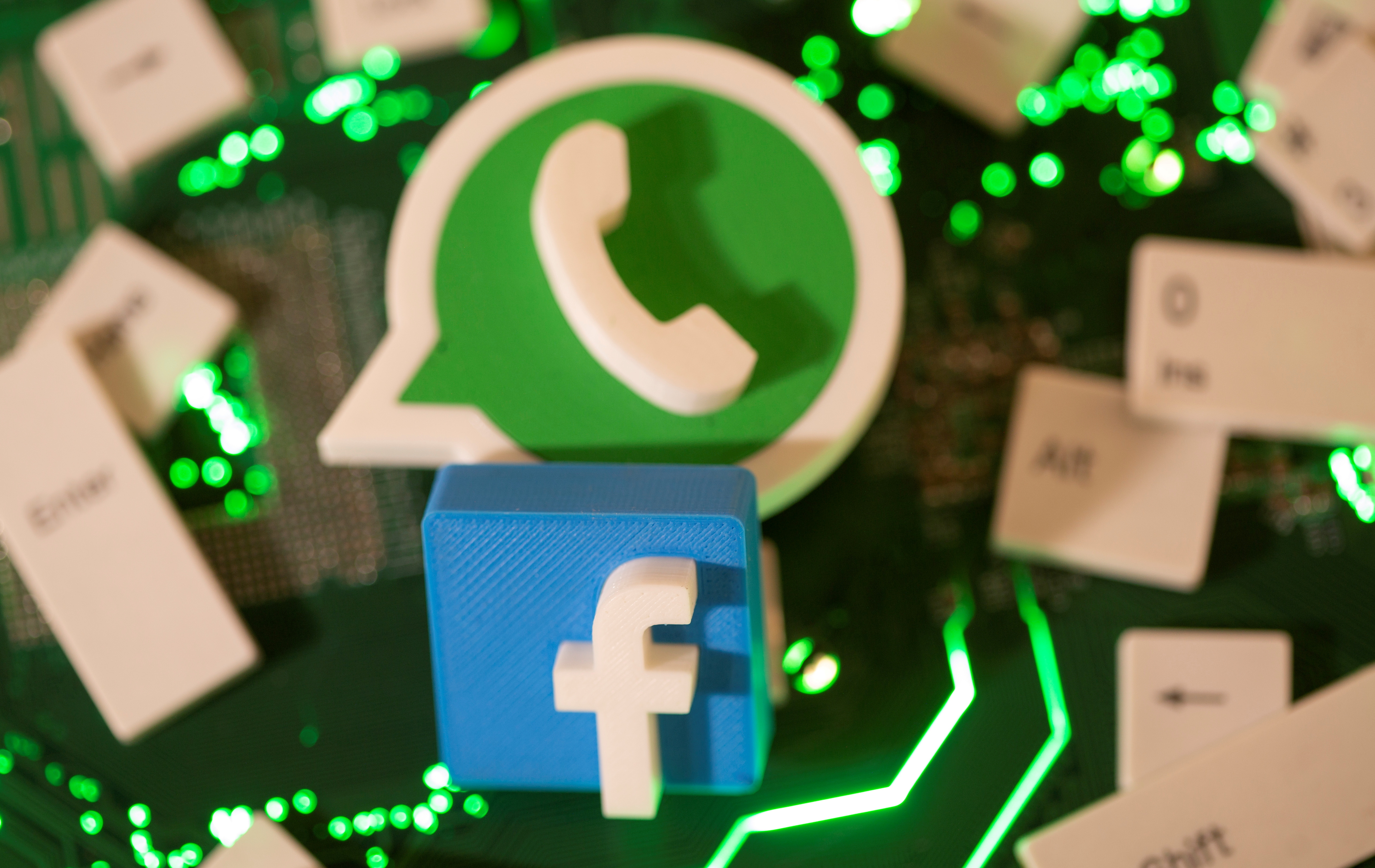 3D printed Facebook and WhatsApp logos and keyboard buttons are placed on a computer motherboard in this illustration taken January 21, 2021. REUTERS/Dado Ruvic/Illustration