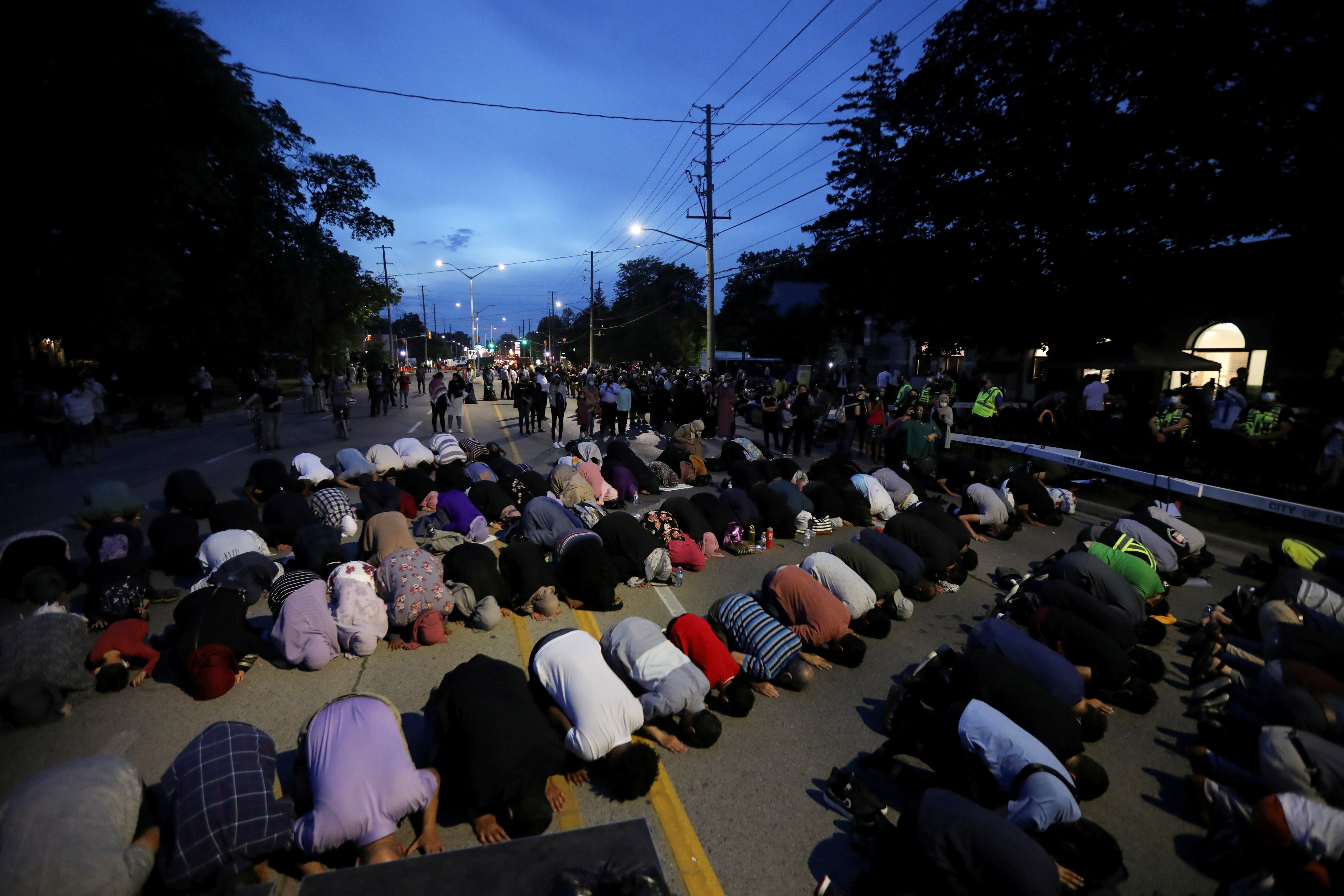 People pray following a vigil after four members of a Muslim family were killed in what police describe as a hate-motivated attack at London Muslim Mosque in London, Ontario, Canada, June 8, 2021. REUTERS/Carlos Osorio/File Photo