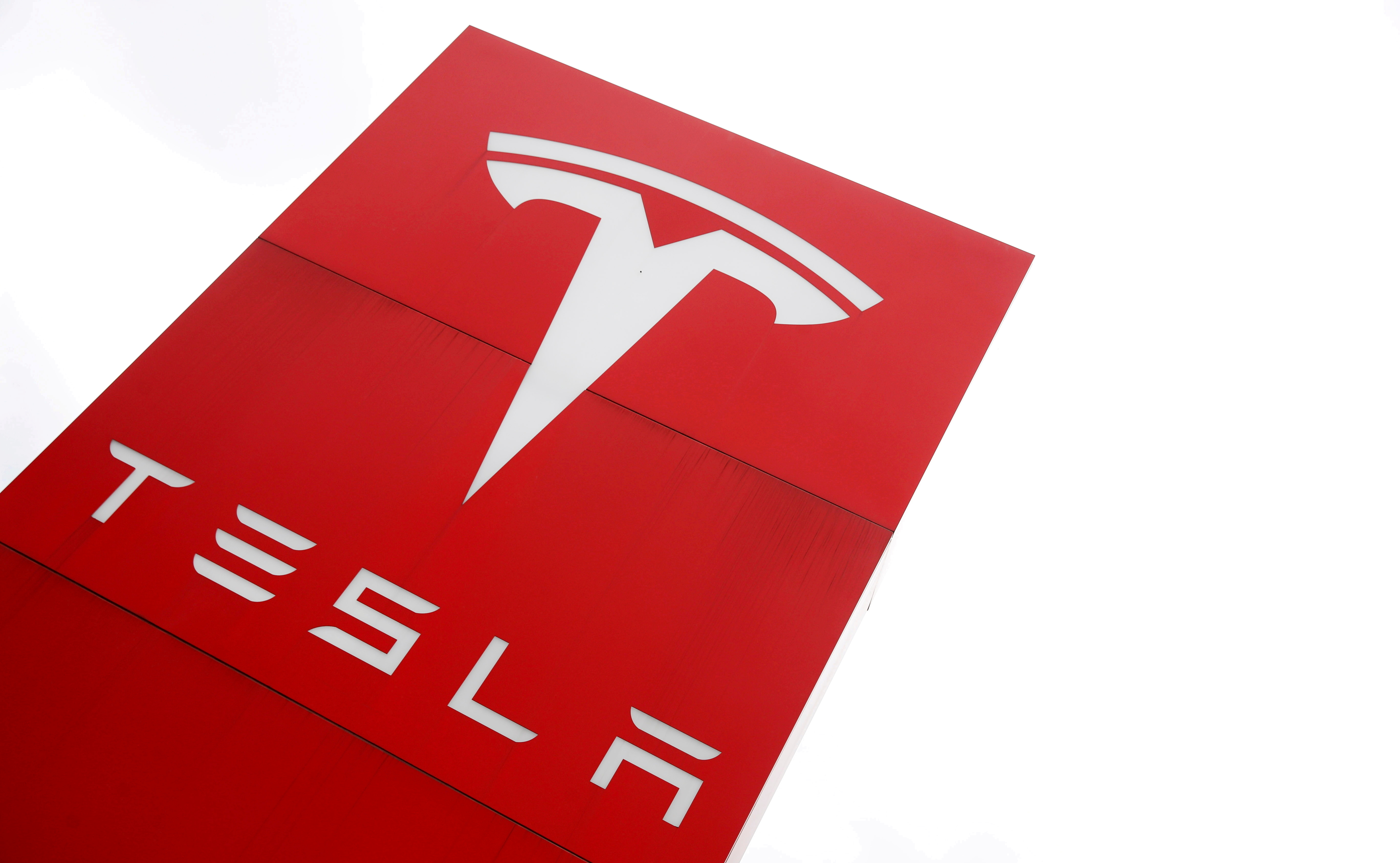 FILE PHOTO: The logo of car manufacturer Tesla is seen at a dealership in London, Britain, May 14, 2021. REUTERS/Matthew Childs/File Photo