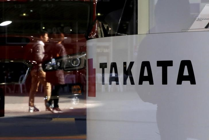 FILE PHOTO -  A logo of Takata Corp is seen with its display as people are reflected in a window at a showroom for vehicles in Tokyo, November 6, 2015. REUTERS/Toru Hanai/File Photo       TPX IMAGES OF THE DAY