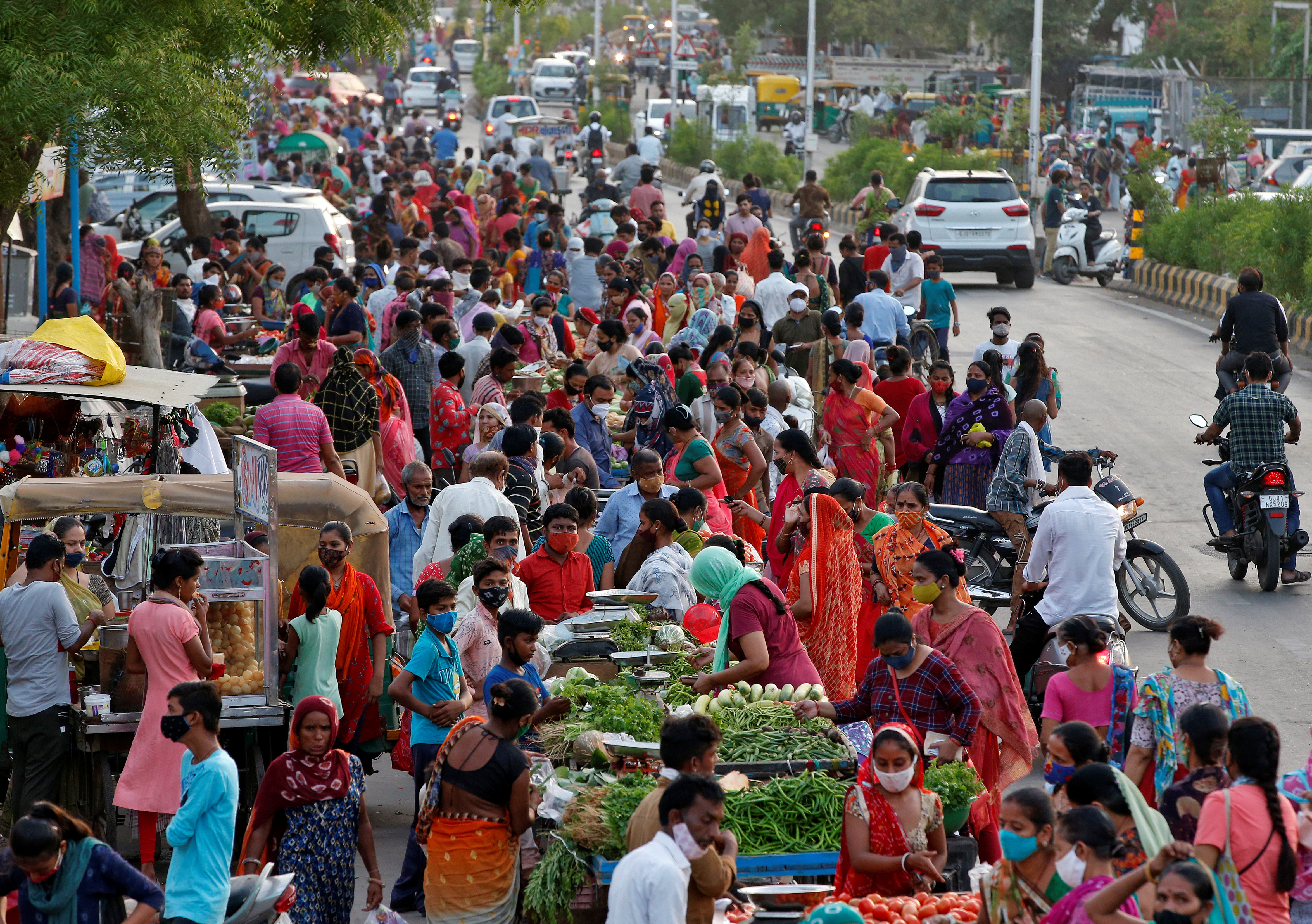People shop at a crowded roadside vegetable market after authorities eased coronavirus restrictions, following a drop in COVID-19 cases in Ahmedabad, India, June 15, 2021. REUTERS/Amit Dave/Files