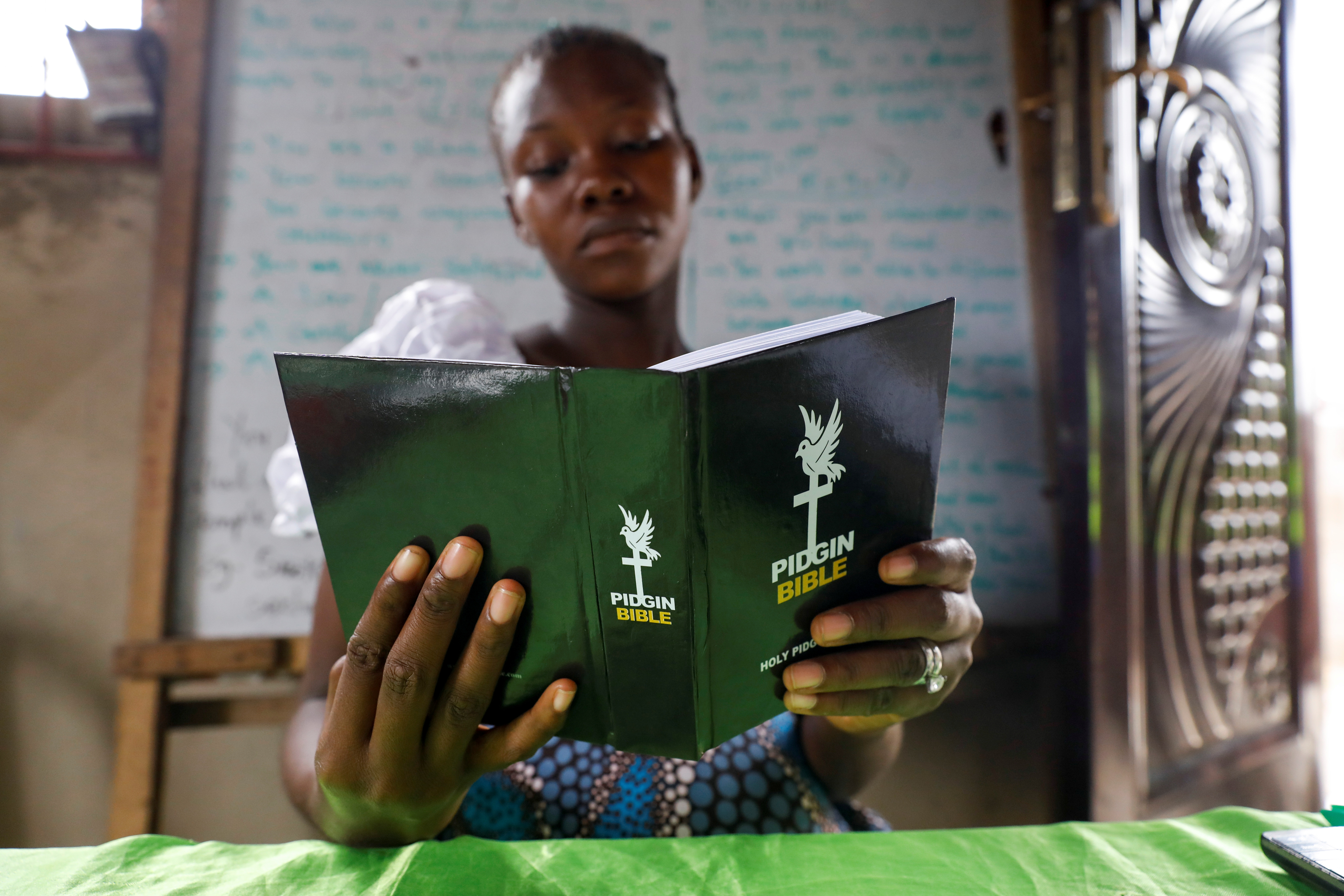 A congregation member reads the Pidgin Bible during a church service at the Heavenly Citizen's Church in Lagos, Nigeria June 27, 2021. REUTERS/Temilade Adelaja