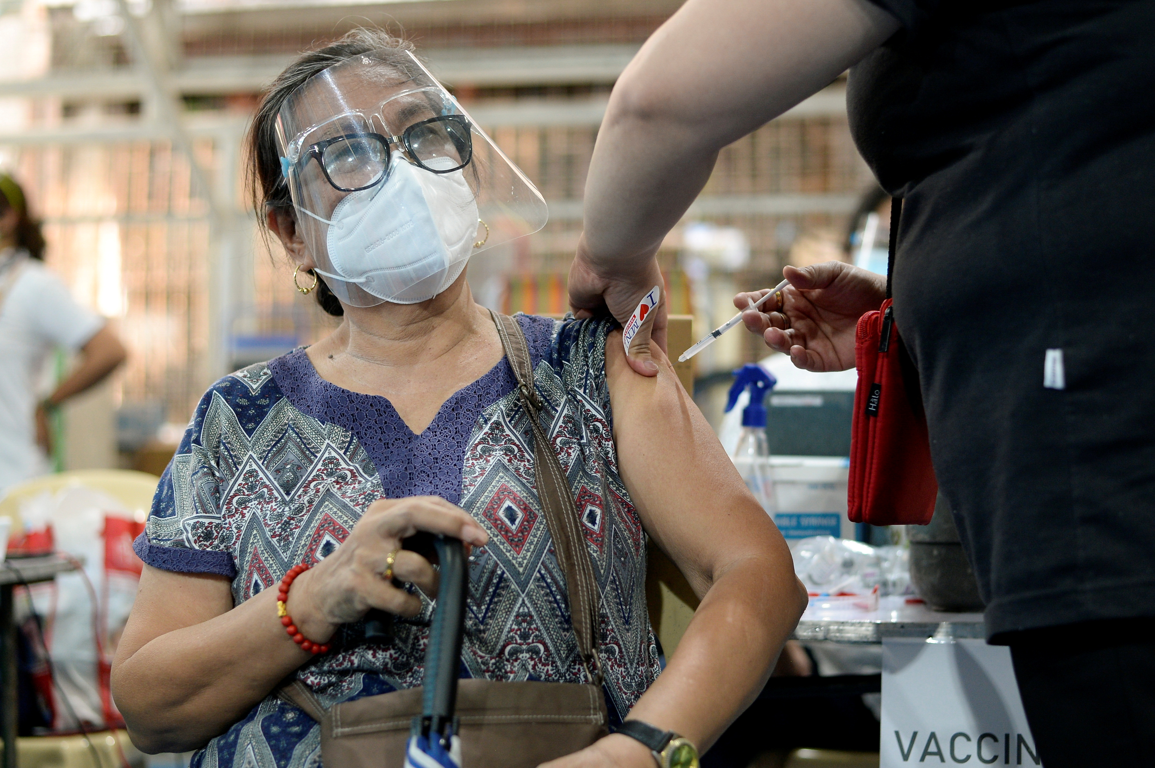 A senior citizen receives her first dose of AstraZeneca coronavirus disease (COVID-19) vaccine, at a covered court in Manila, Philippines, March 29, 2021. REUTERS/Lisa Marie David/File Photo