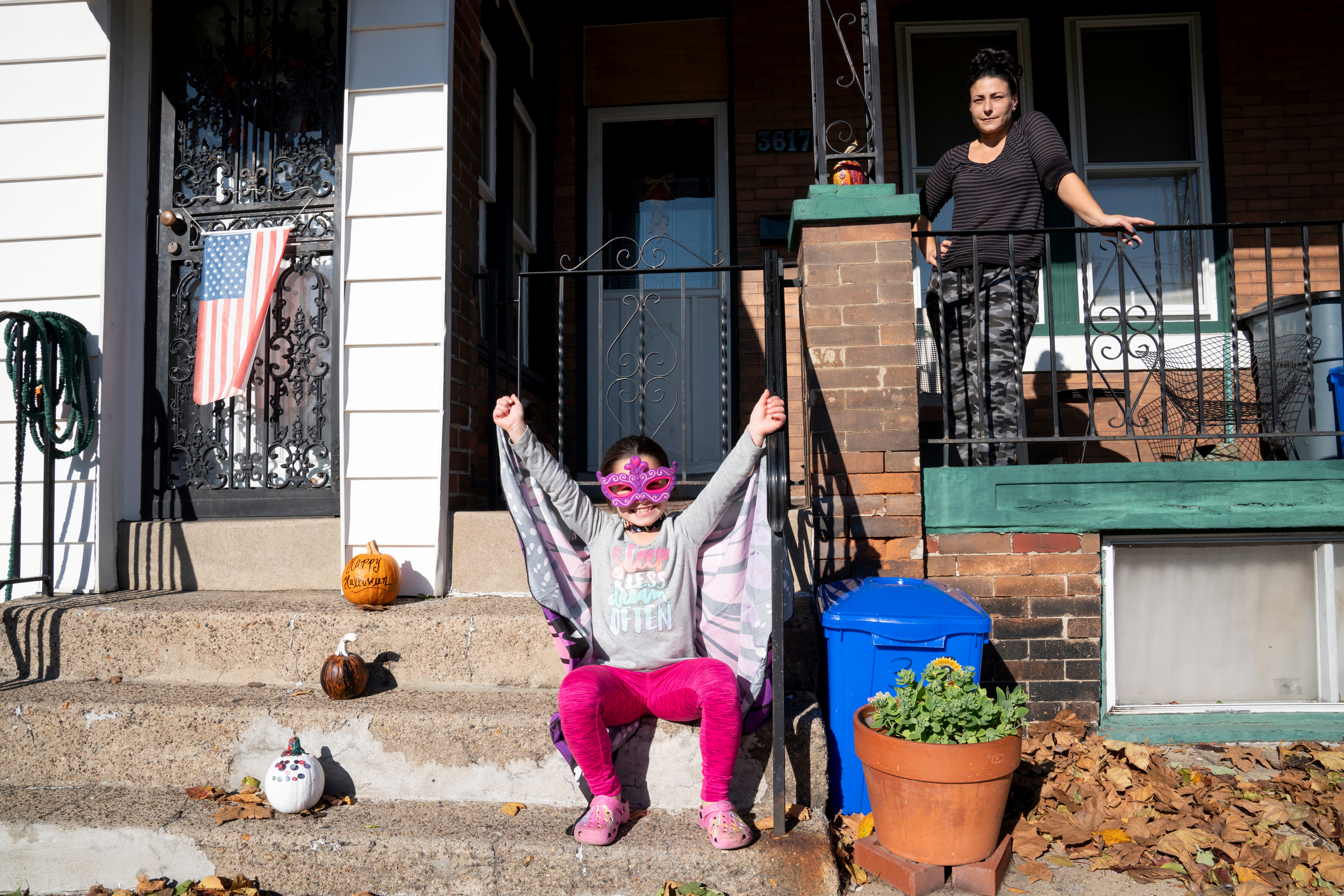 Jenny Snider, 39, and daughter Ellie Sagna, 7, pose for a photo in front of their house in Forgotten Bottom next to the PES Refinery in Philadelphia, Pennsylvania, U.S., November 2, 2020. REUTERS/Dane Rhys