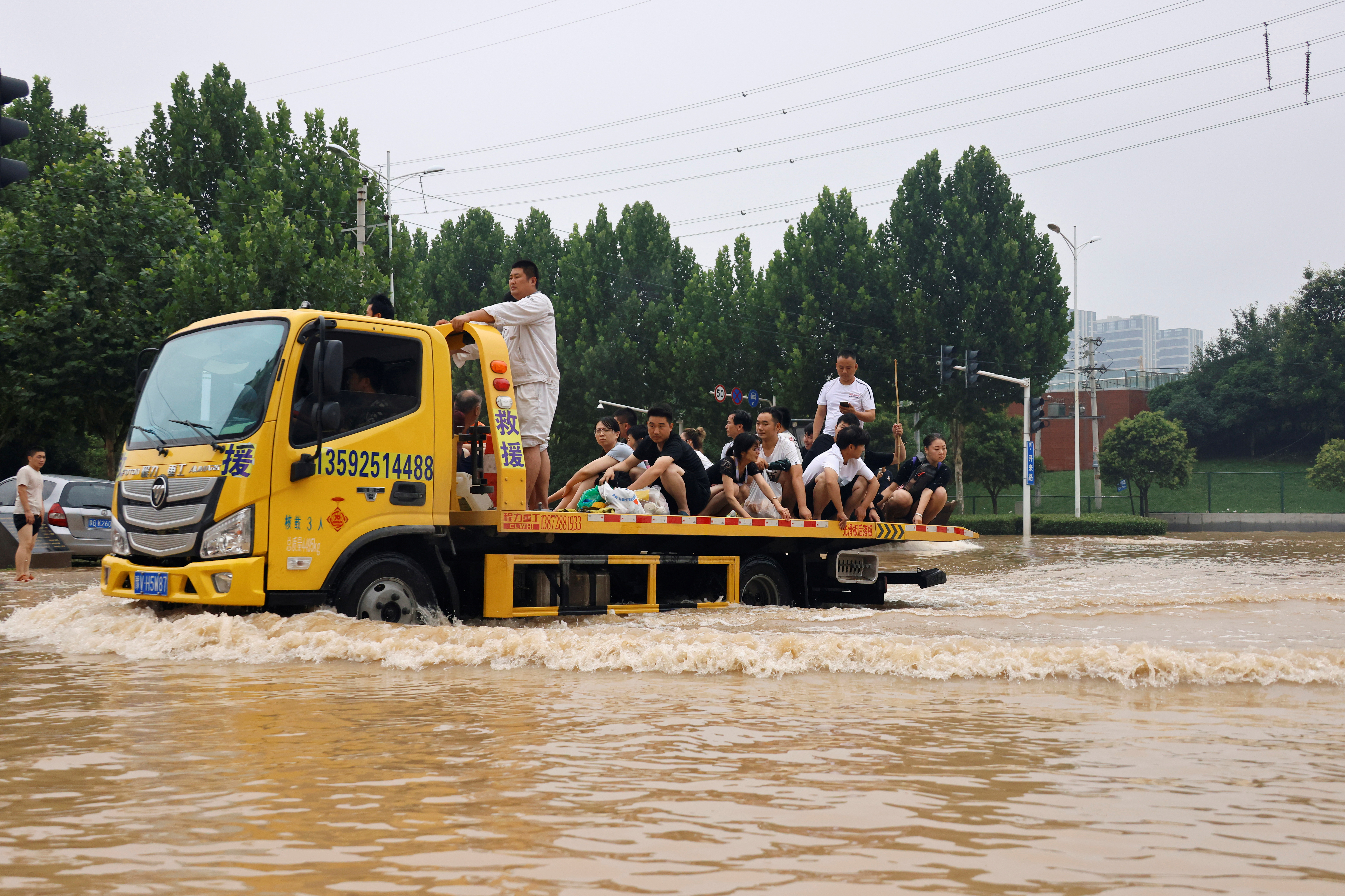 People ride on the back of a truck as they make their way through floodwaters following heavy rainfall in Zhengzhou, Henan province, China July 23, 2021. REUTERS/Aly Song